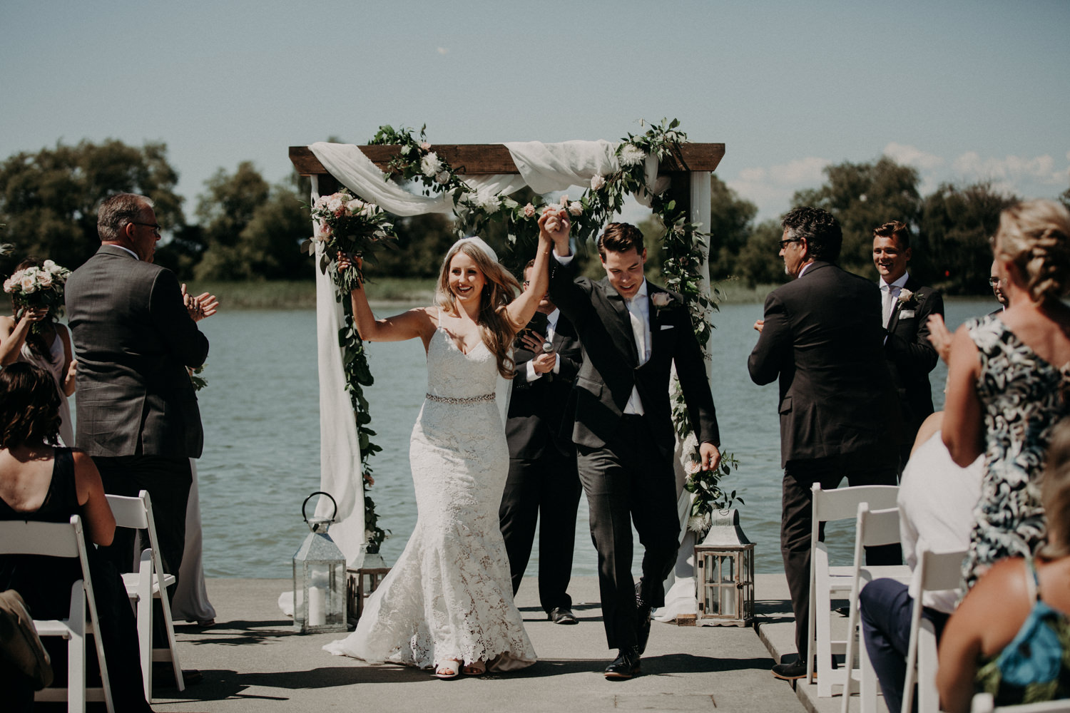 The bride and groom celebrate as they exit their ceremony at the UBC boathouse in Richmond, BC.