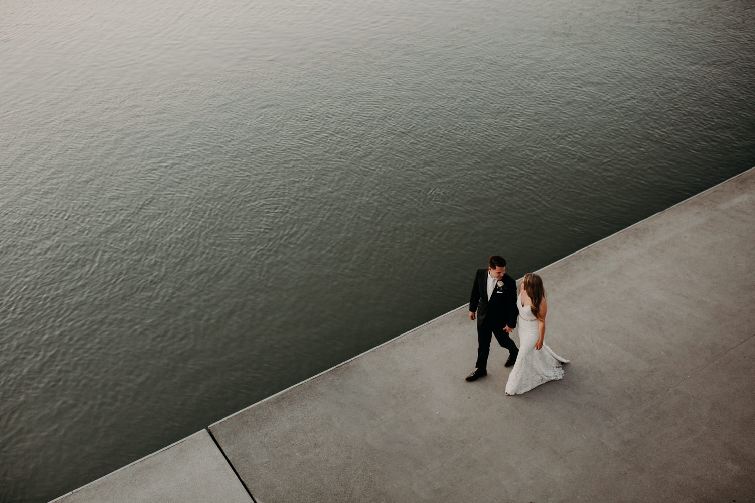A photo taken from above as the bride and groom walk along the river at the UBC Boathouse in Richmond, BC.