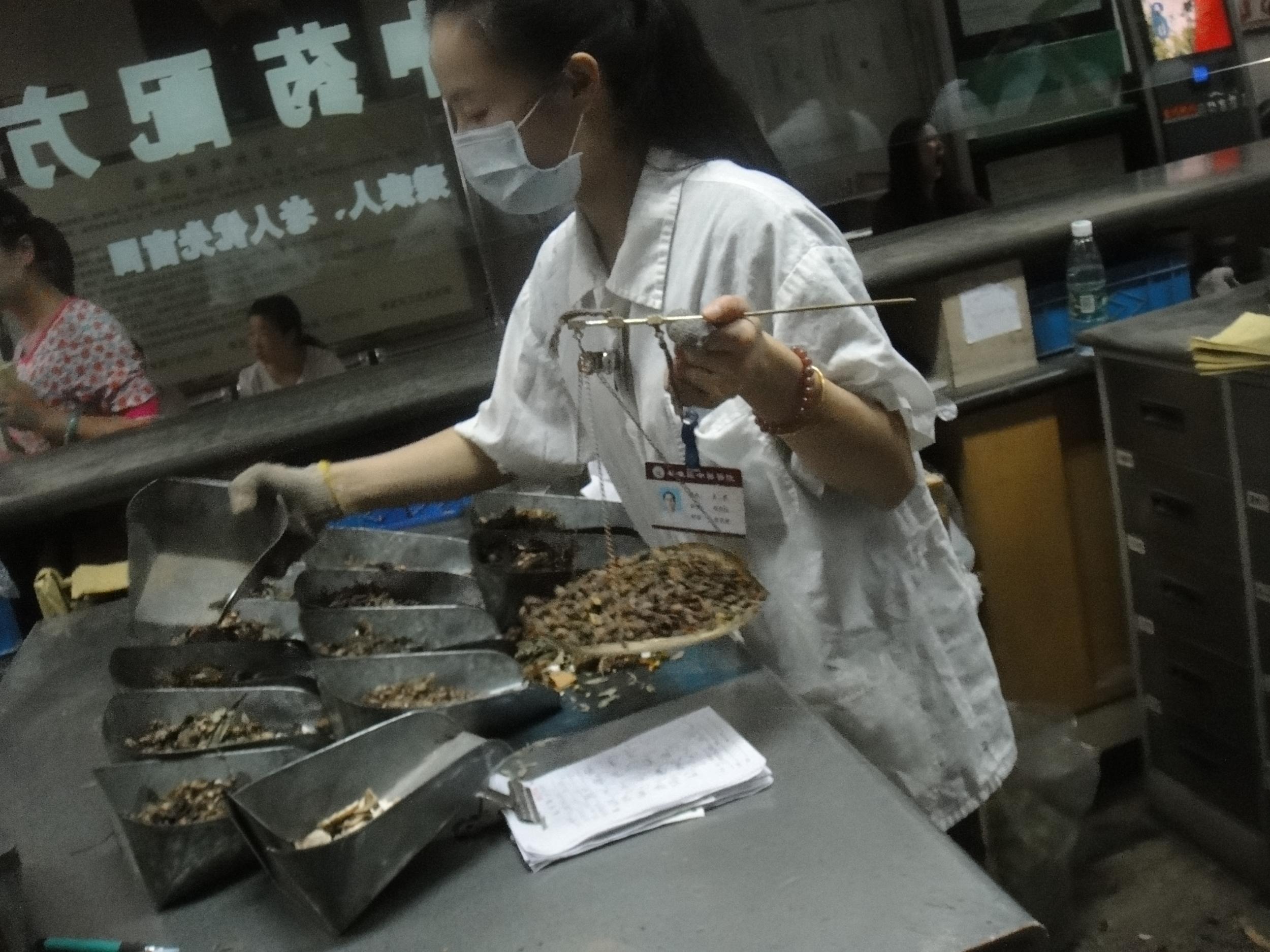 A woman weighs and dispenses Chinese herbs at Qin Huai Hospital in Nanjing, China.