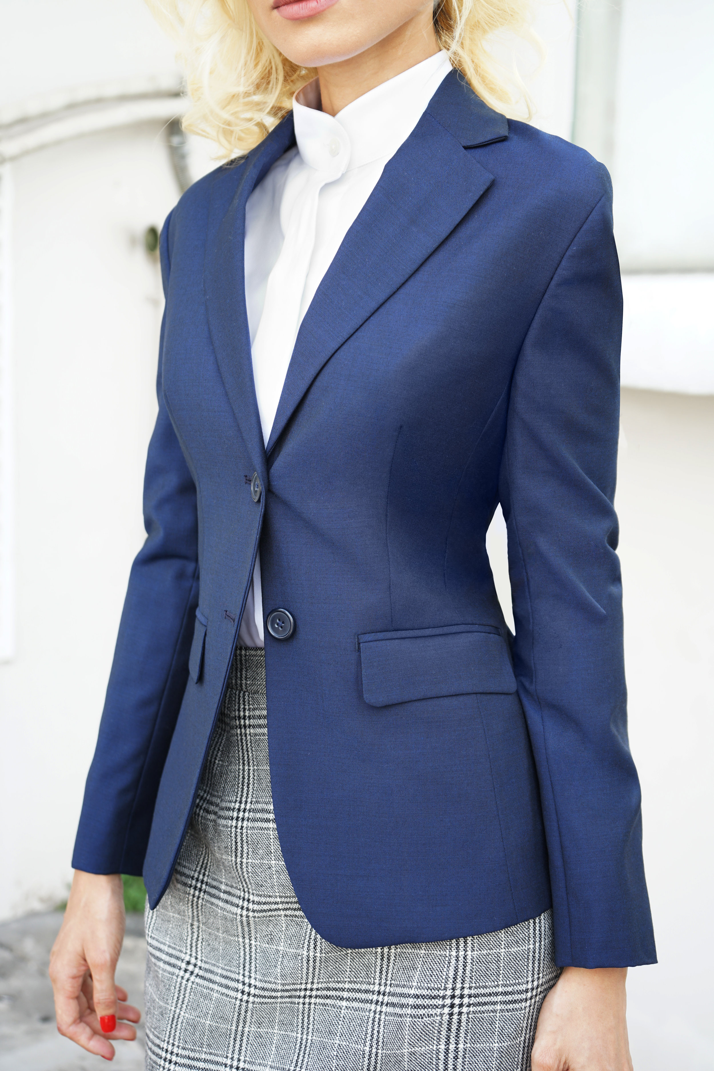 Woman's blue suit jacket with a Price of wales skirt