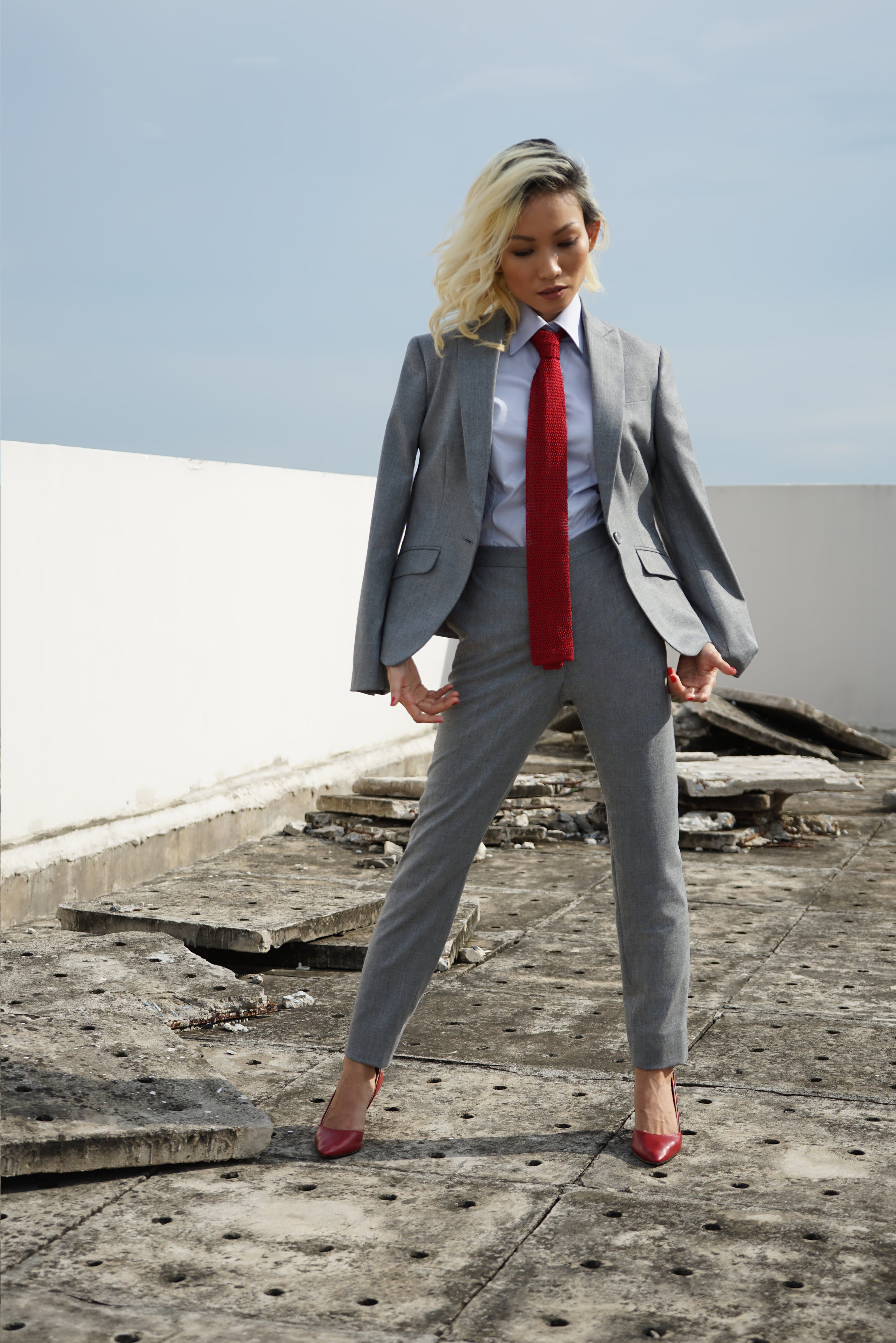 ladies' light grey pant suit with red tie and heels