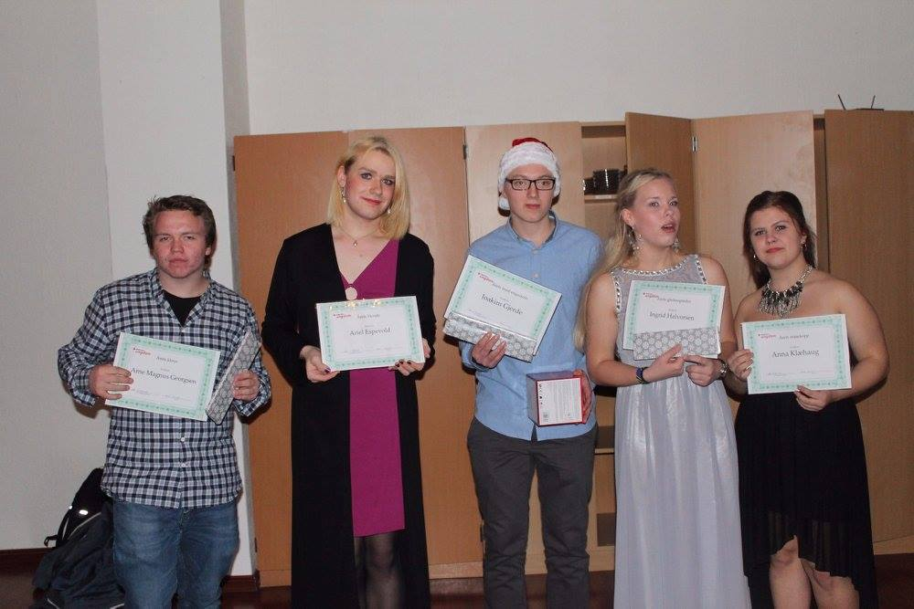 Five youth volunteers holding their certificates and gifts