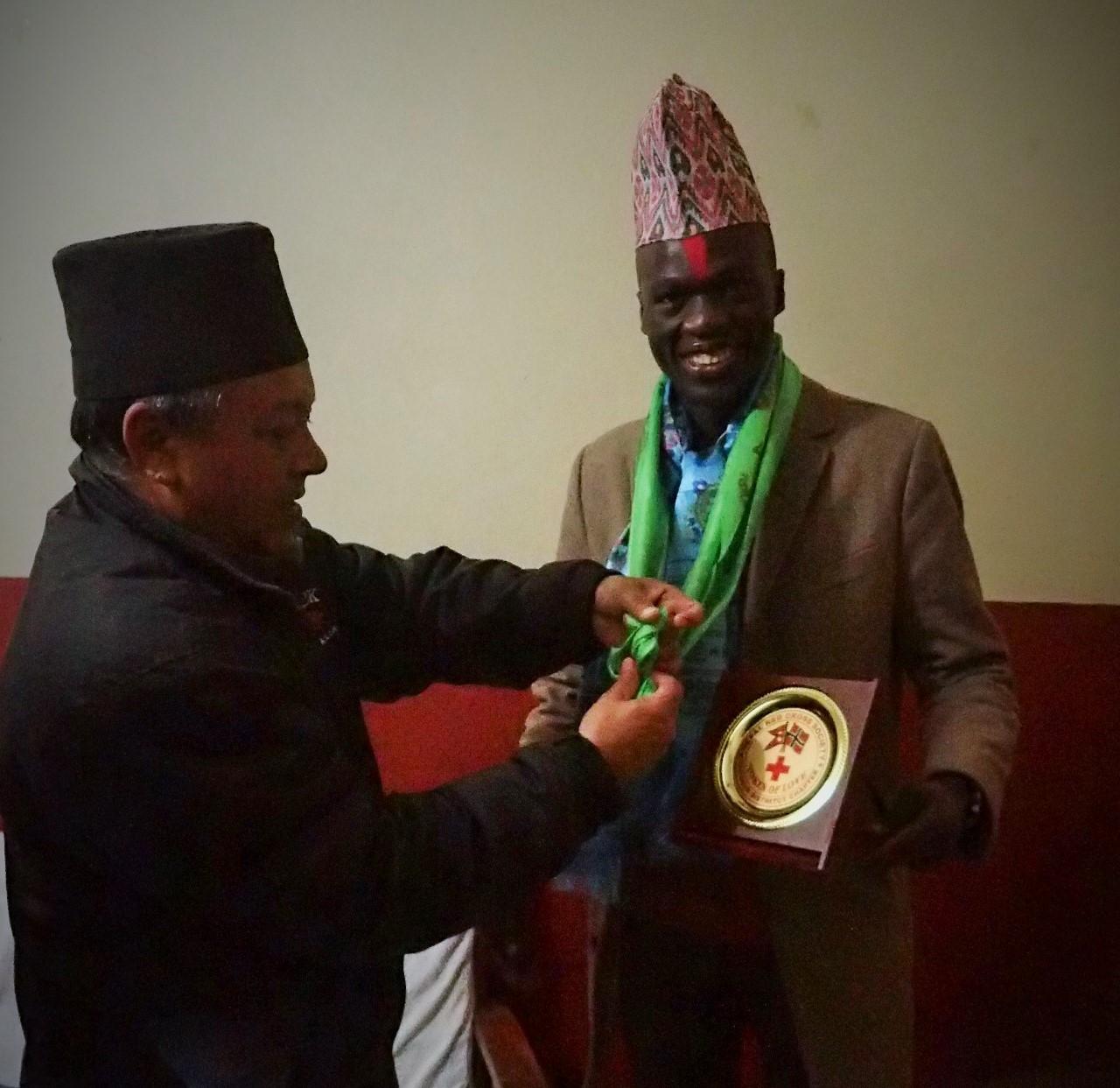 Juma Sir receiving token of love from the Red Cross Tanahun District President, Gauli Sir.