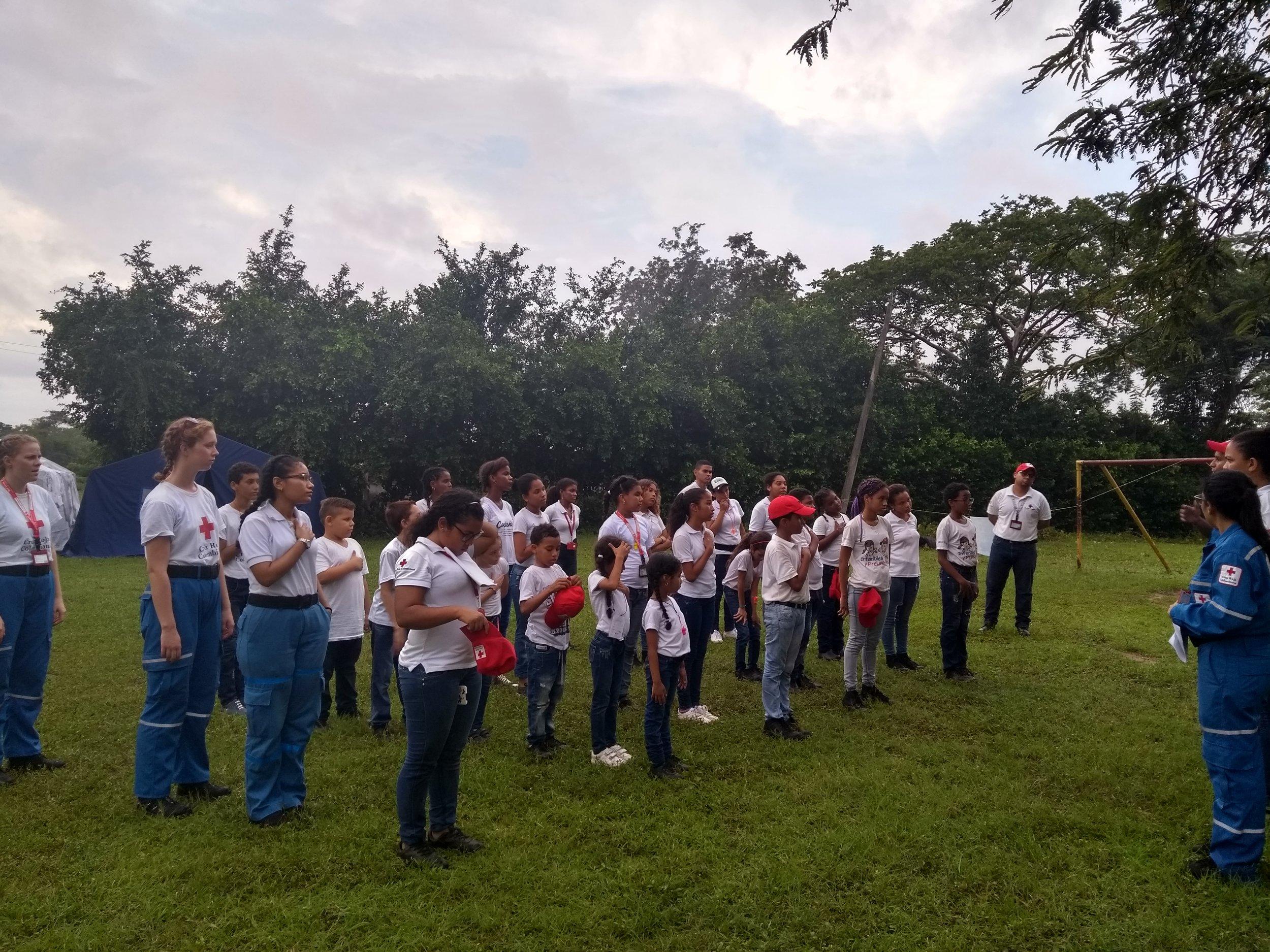 Los participantes cantan el himno de la Cruz Roja antes de que puedan comenzar las actividades.