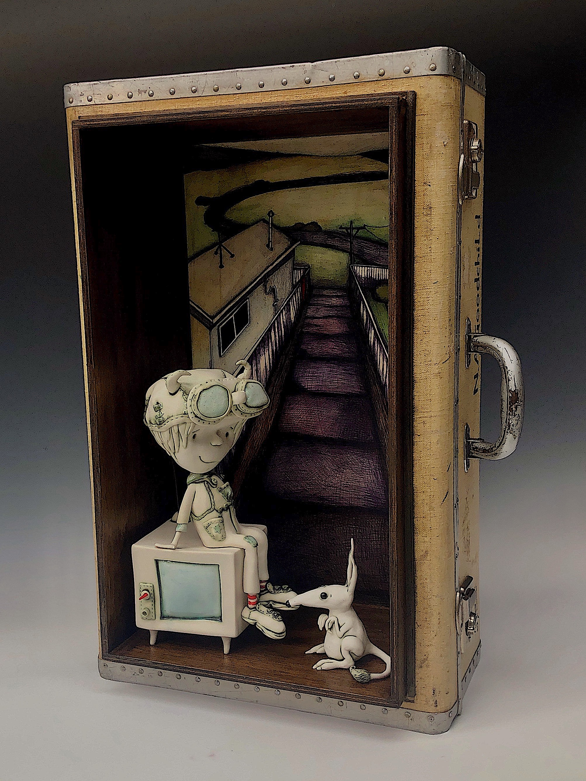 Title : 'The road no one seems to take anymore.' w34cm x 67cm x 27cm Material : found suitcase, porcelain, illustration Wall mounted