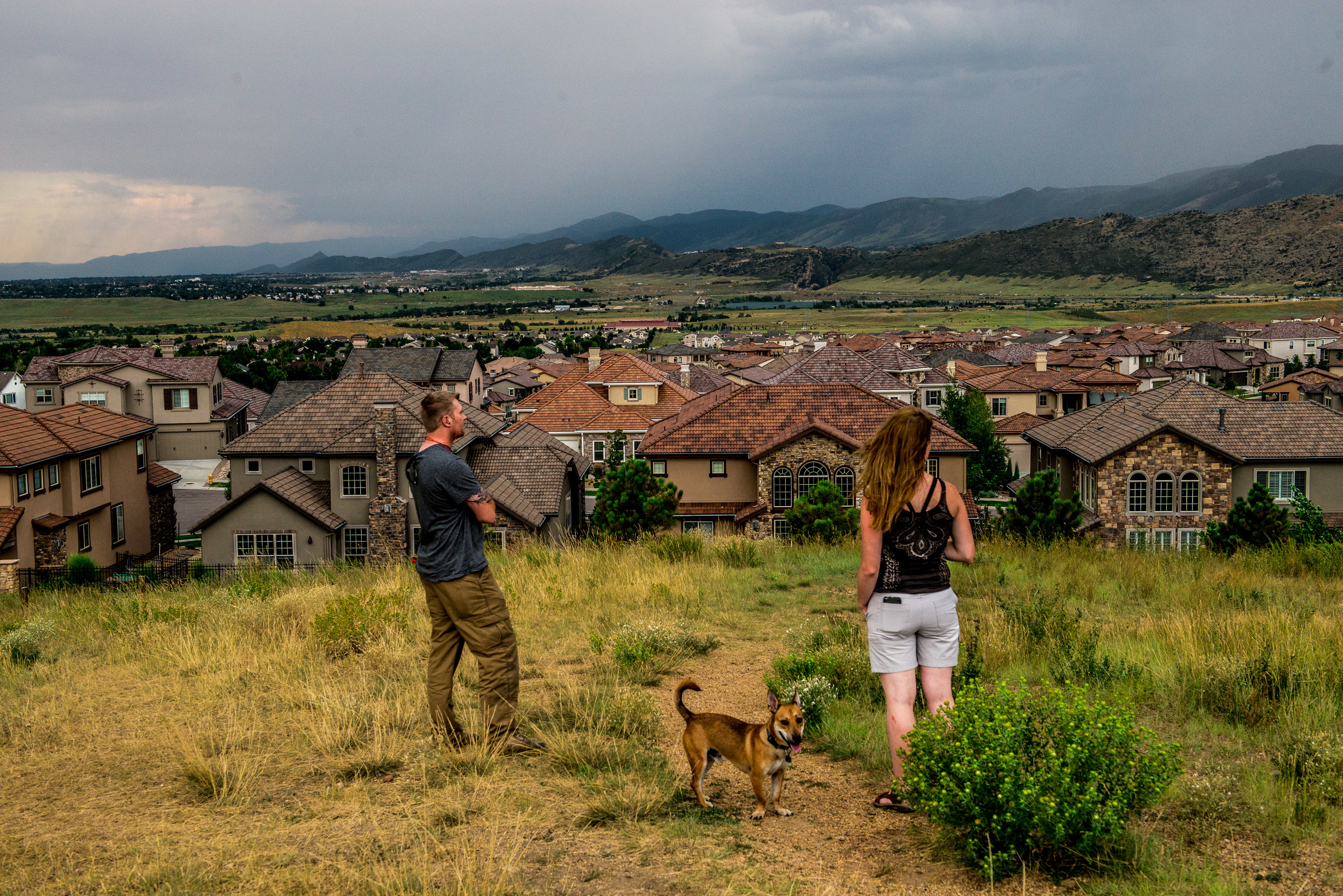 A couple and their dog at the Solterra dog park overlooking the homes.