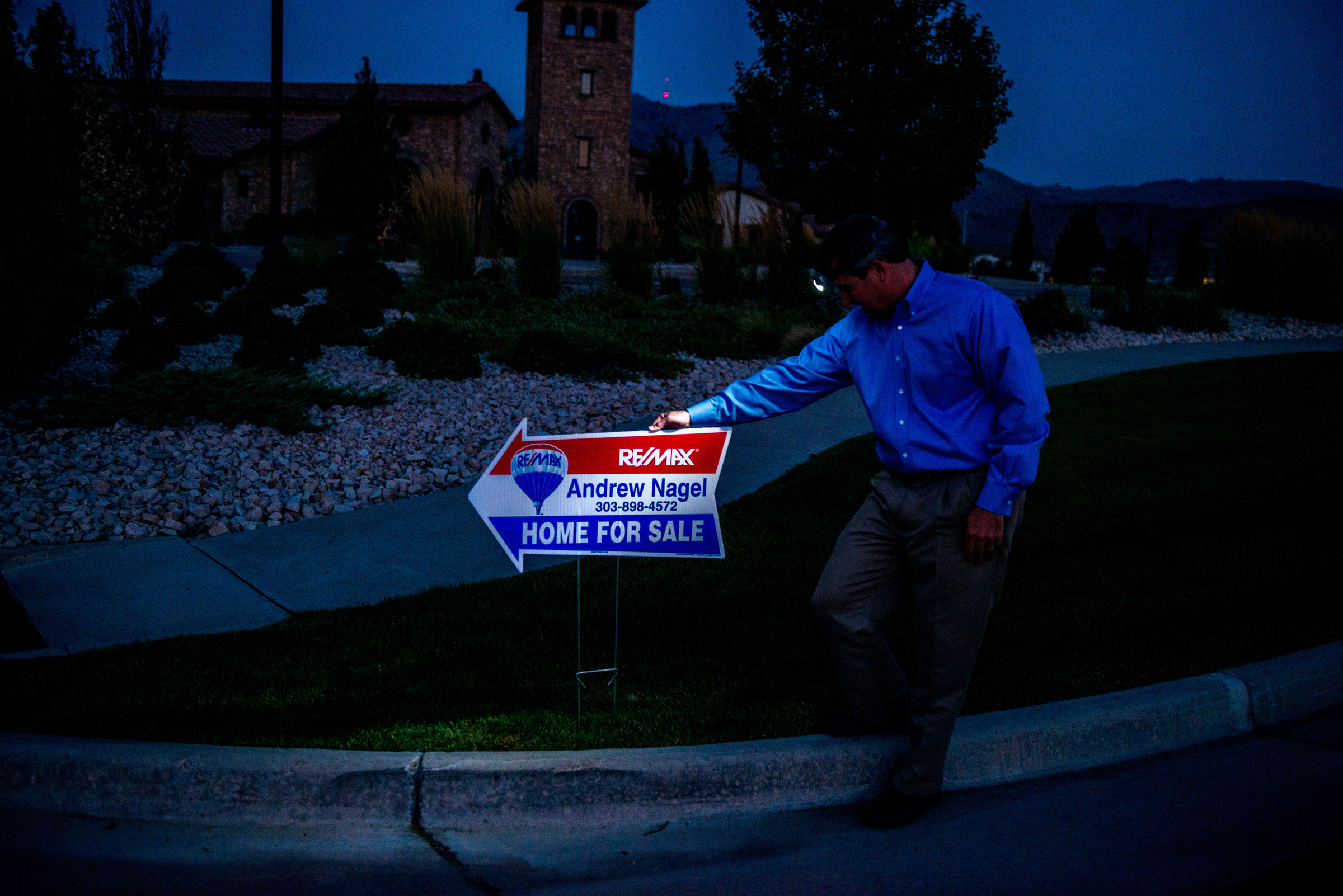 Andrew Nagel Realtor putting out signs in the dark.