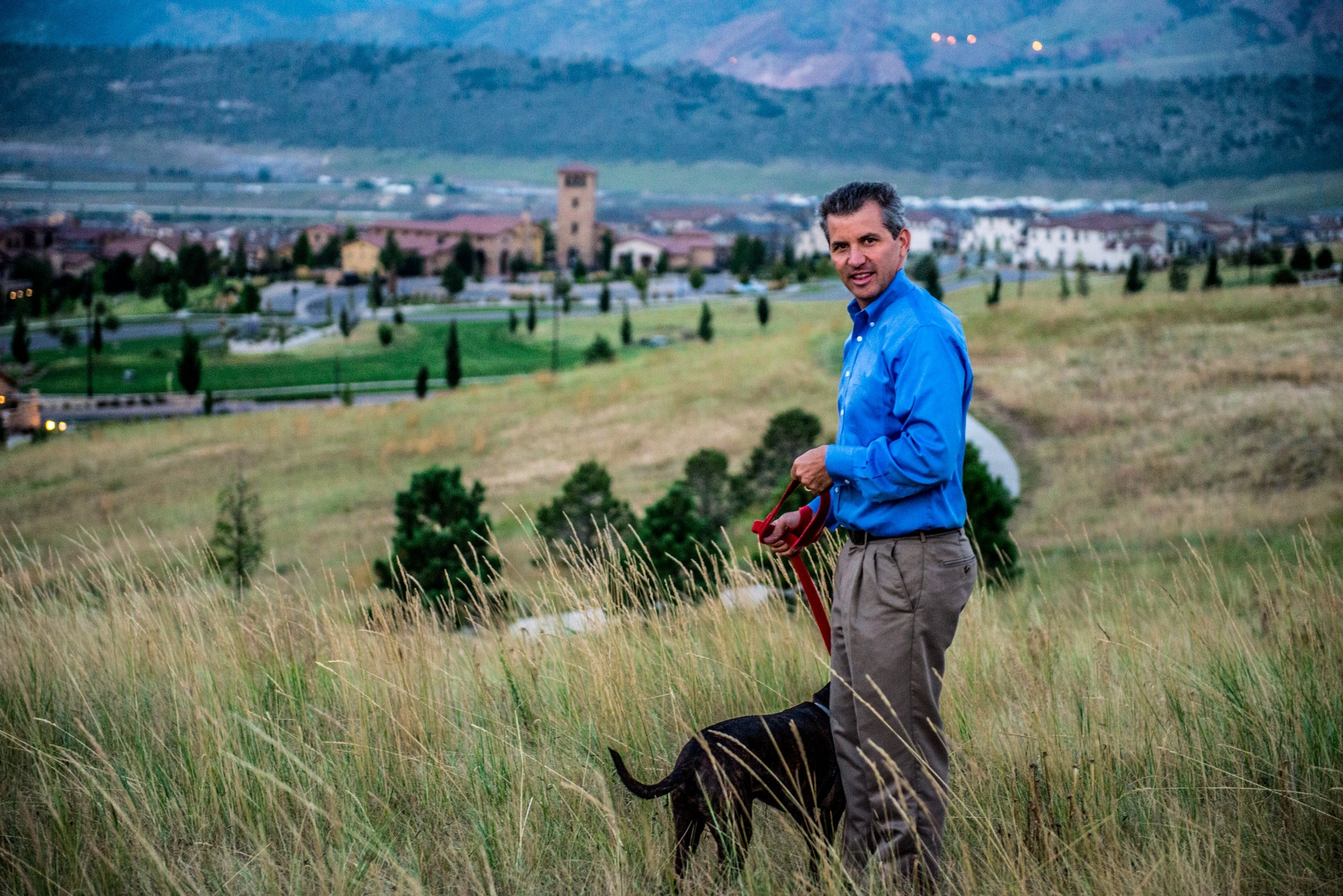 Re/Max realtor Andrew Nagel with his dog in the open space overlooking Solterra