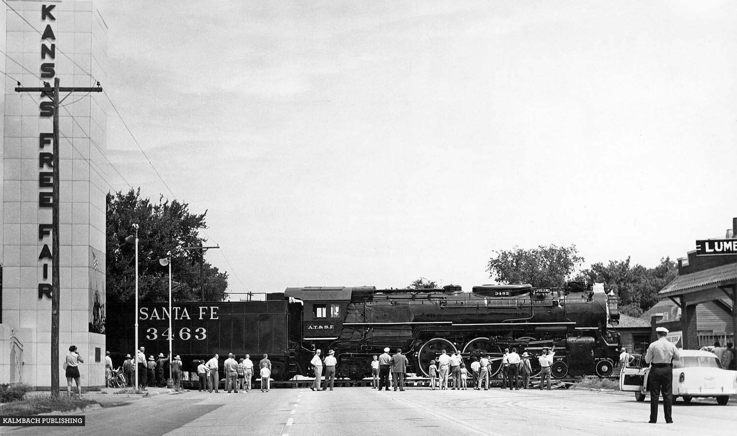 Blocking the road for only 90 minutes the ATSF shoved locomotive 3463 into the Kansas Free Fair grounds using an idler flat car (visible in front of the steam engine) and a diesel-electric switch engine. Image courtesy of Kalmbach Publishing Co.
