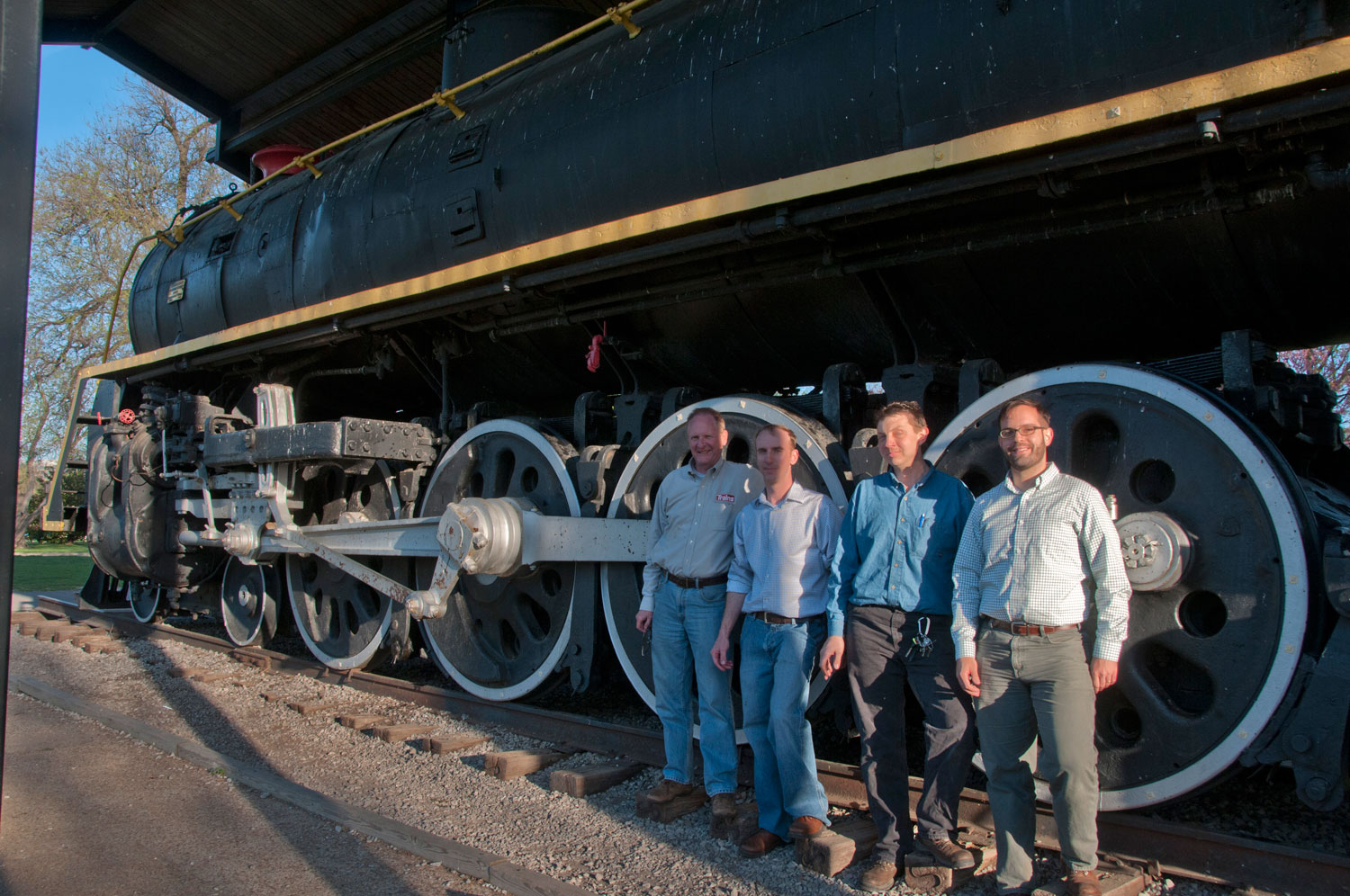 "The ""Stripe"" with a few of the NSPS folks in front of its 70"" driving wheels. From left to right: Jim Wrinn [Editor of Trains Magazine & NSPS Board Member], Shane Meador [NSPS President], Jason Sobzynski [Steam Mechanic and NSPS Advisor] and Davidson Ward [CSR President and NSPS Advisor]. Photo: S. Ward"