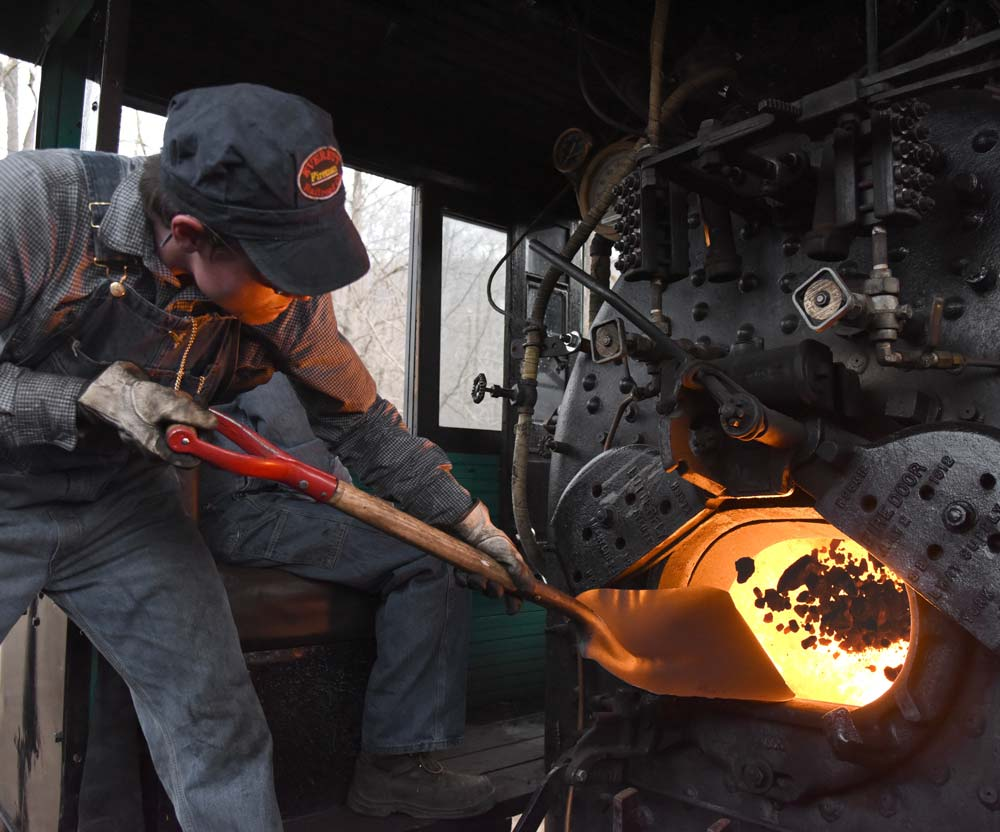EVRR fireman Stephen Lane shovels a scoop of coal into the firebox of No. 11 during a trip in December 2015. Photo by, and used courtesy of, Oren B. Helbok.