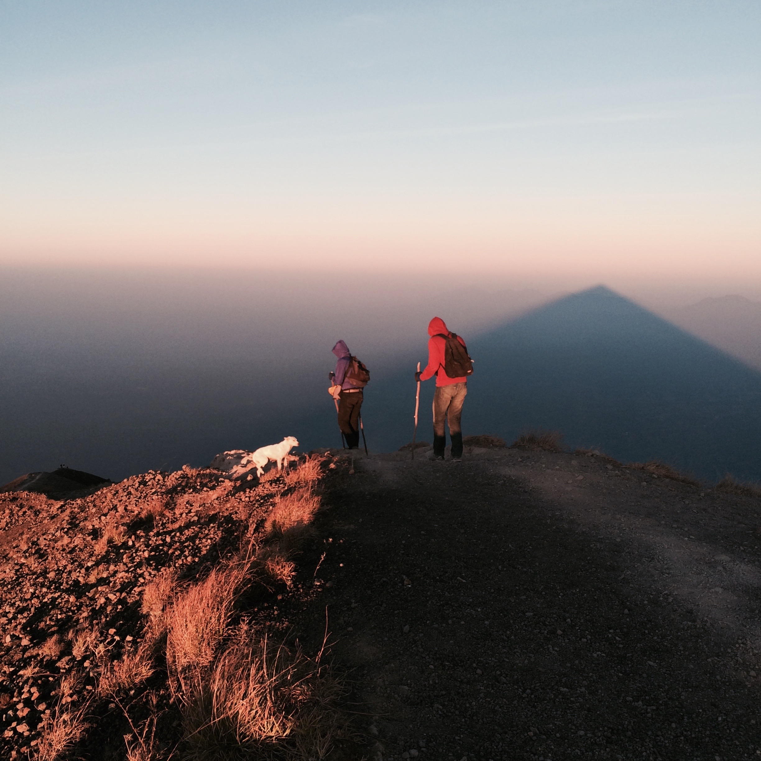 Hikers and the shadow of Mt Agung from the morning sun on clouds