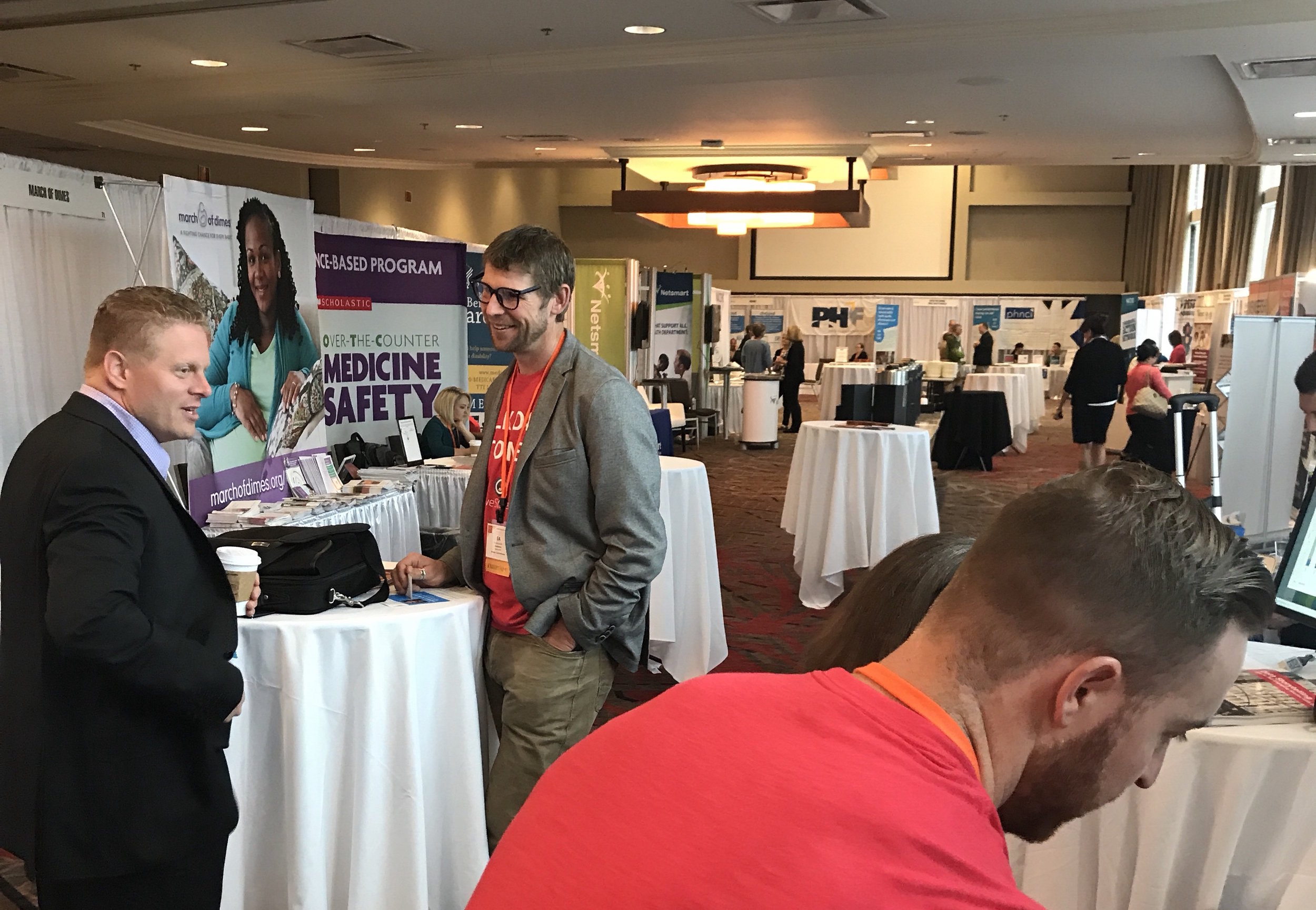 Cory Kendrick (left), Director of Population Health with Summit County, OH, speaks with LiveStories' Director of Partner Engagement, EA Weymuller at the 2017 NACCHO conference. In the foreground, ADR Ryan Gibson shows the LiveStories platform in action.