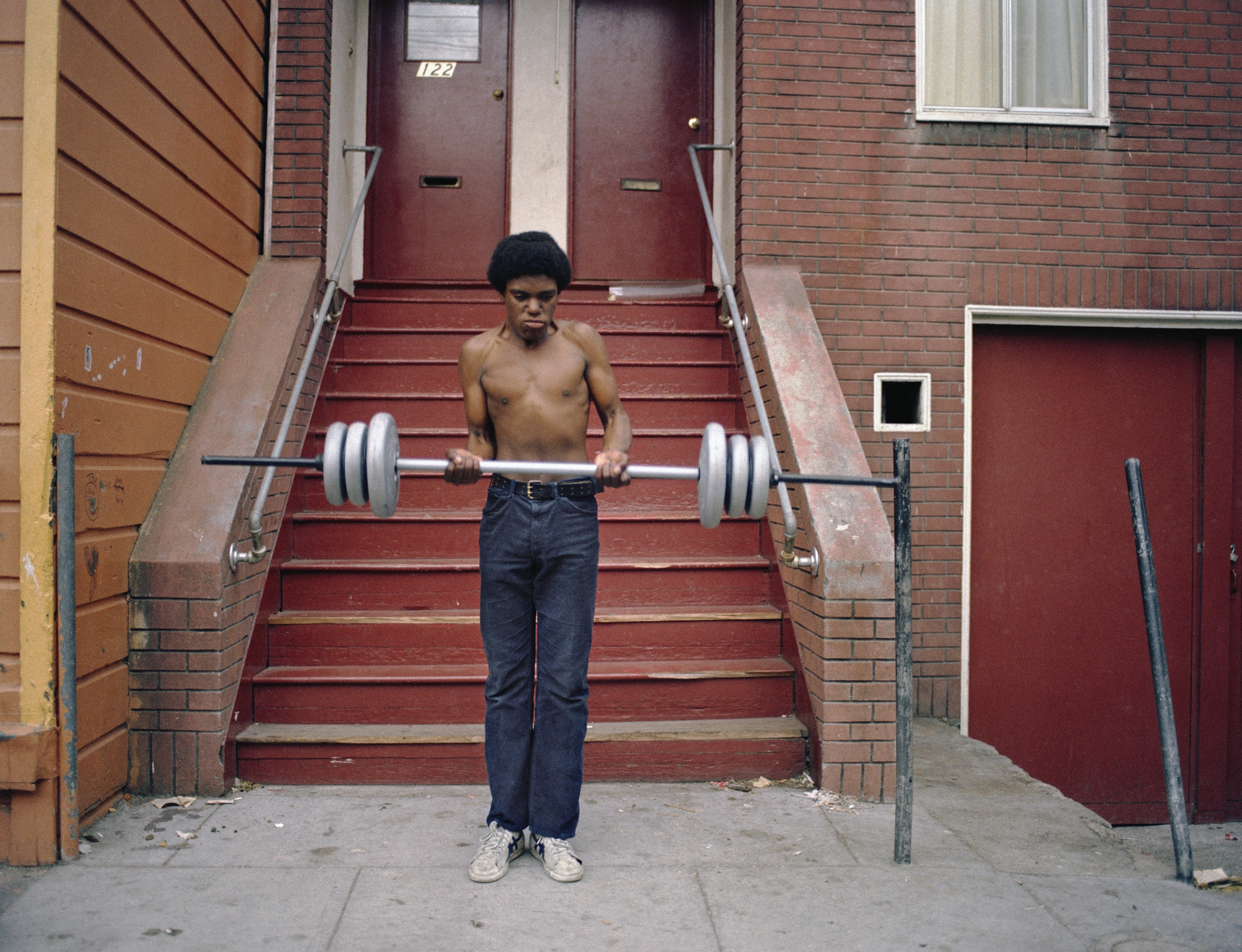 JANET DELANEY Boy lifting weights, 122 Langton Street, 1979 Archival Pigment Print, 2016 16 x 20 inches, edition of 5 20 x 24 inches, edition of 2 30 x 40 inches, edition of 2