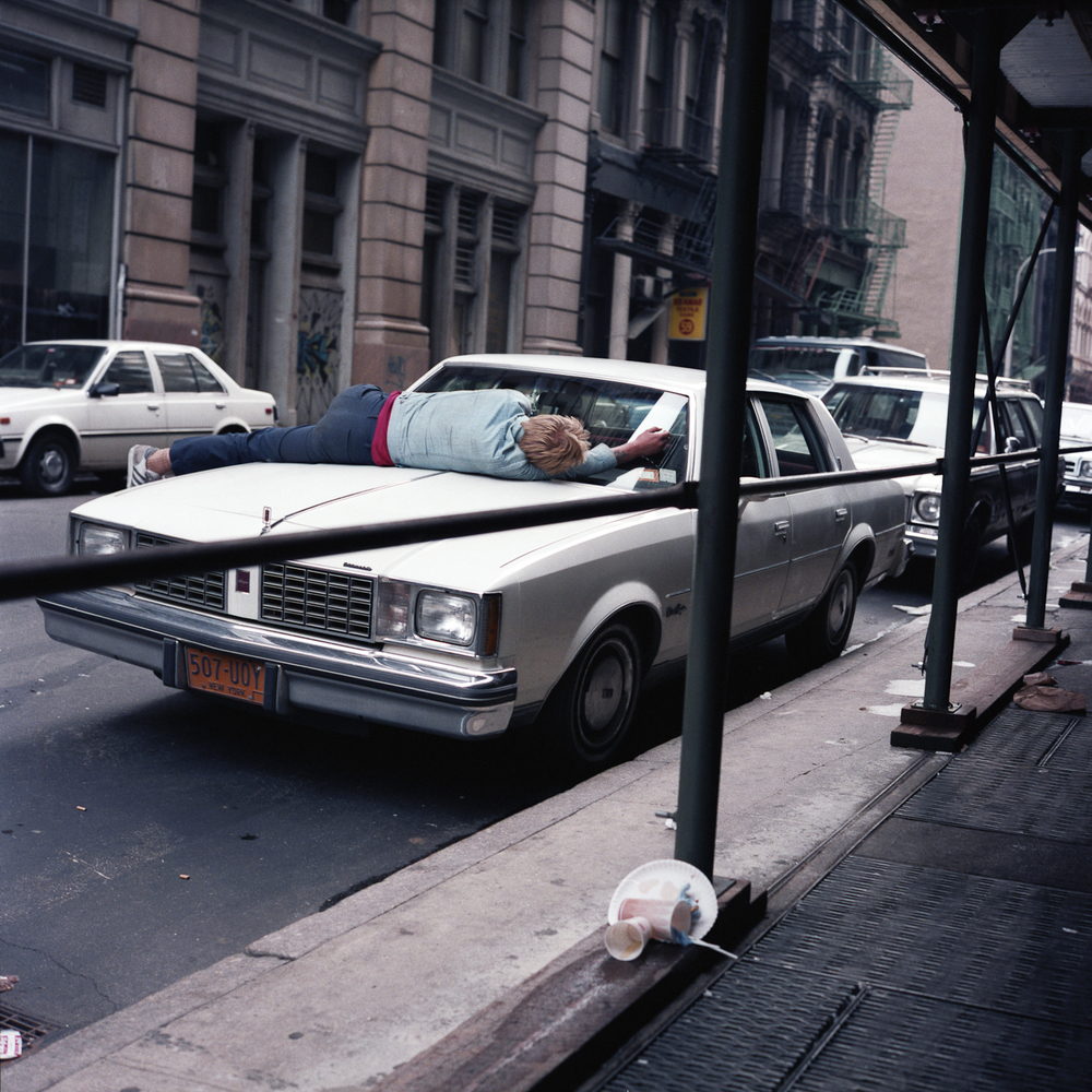 JANET DELANEY Man Asleep on Car, 1985 from New York City 1984-1987 Archival Pigment Print 15 x 15 inches, edition of 5 24 x 24 inches, edition of 2