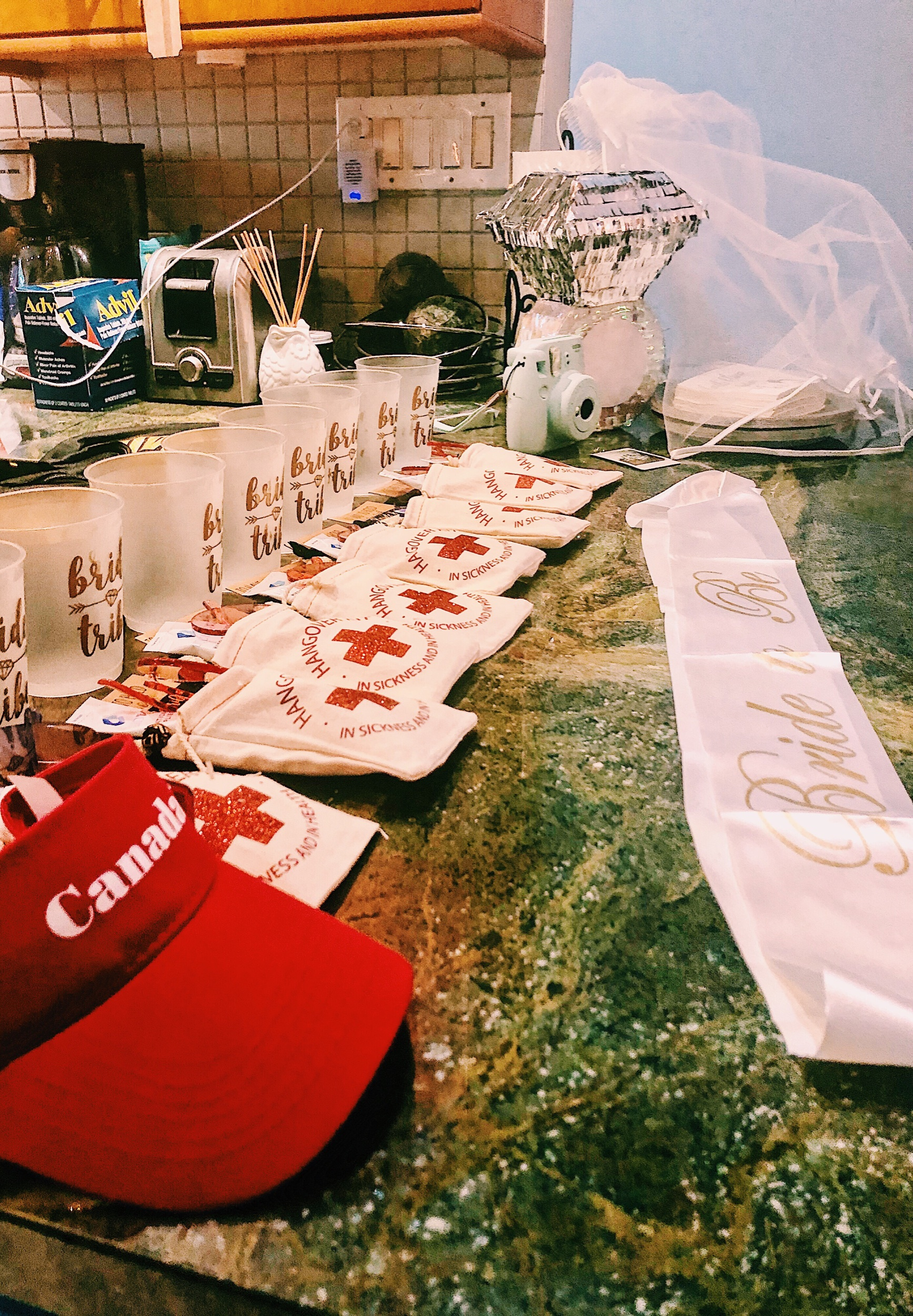 "A Canada visor, ""Bride Tribe"" cups, a ring piñata, a white ""Bride to Be"" sash, and of course, hangover kits 😂😜"