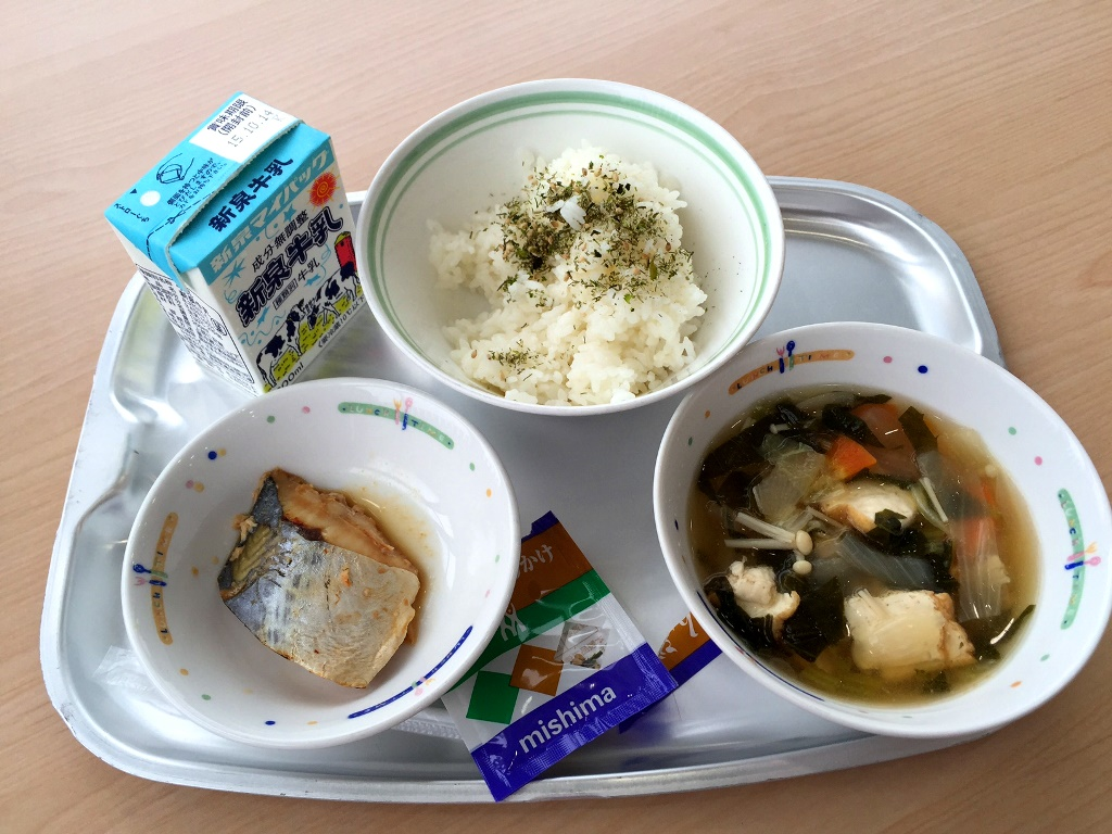 Grilled herbed fish, rice with seaweed and sesame garnish, tofu and vegetable soup with a carton of milk.