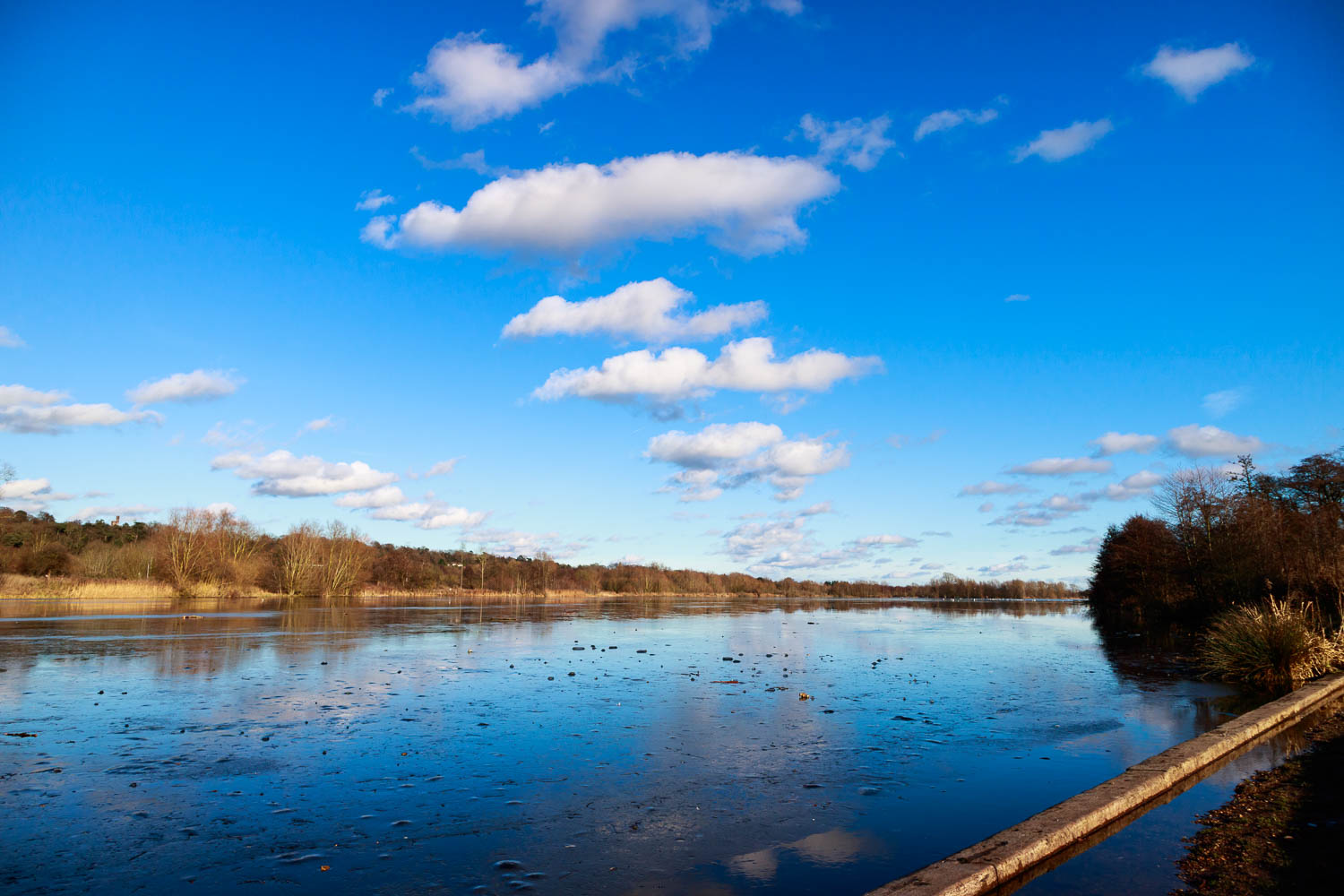 A mostly frozen Whitlingham Broad under a bright sky.