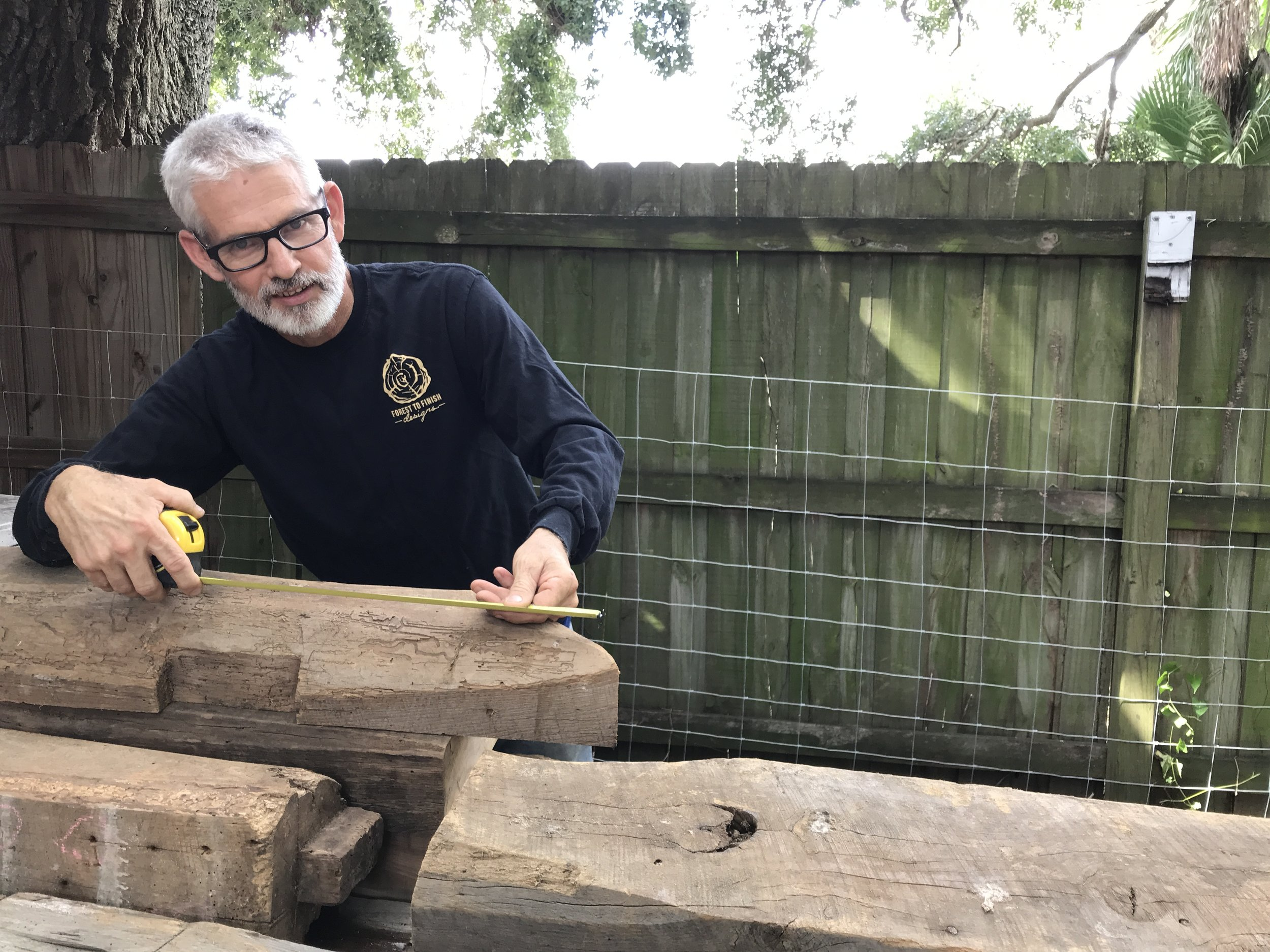 David Gay, owner, searches for and measures the perfect piece of wood for a project.