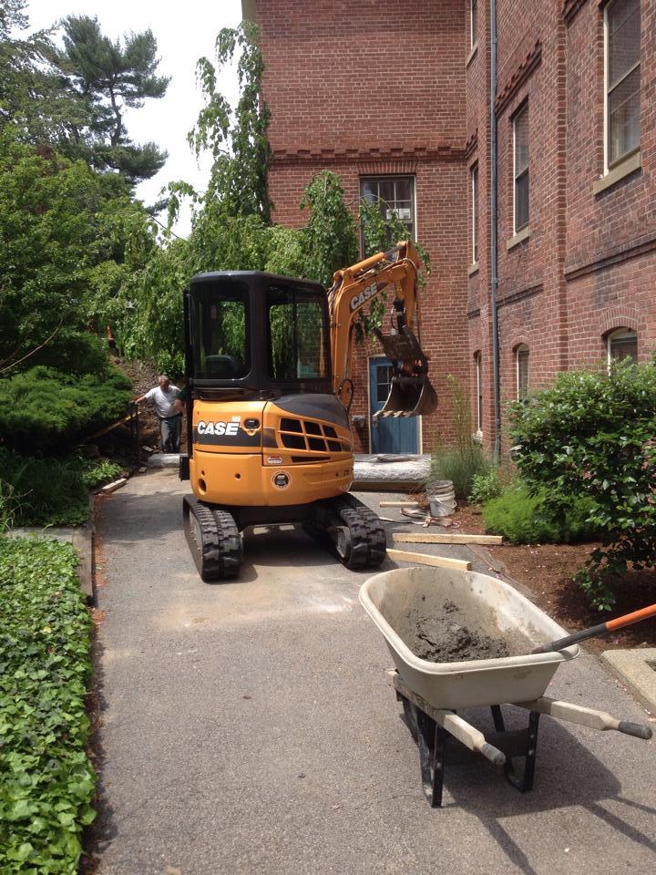 Excavator installing granite steps