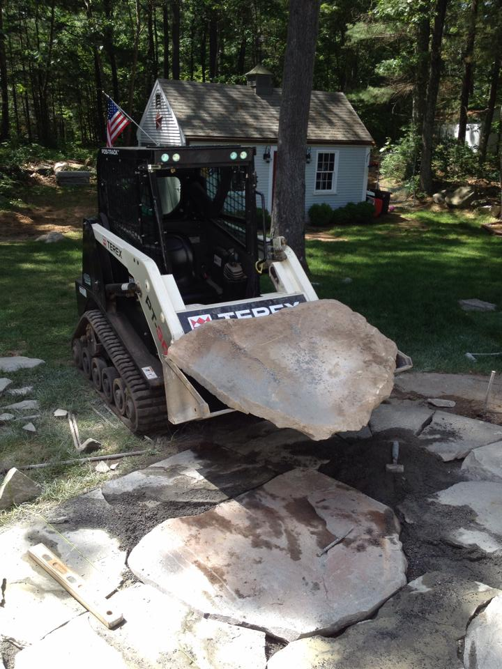 Skidsteer moving fieldstone into place