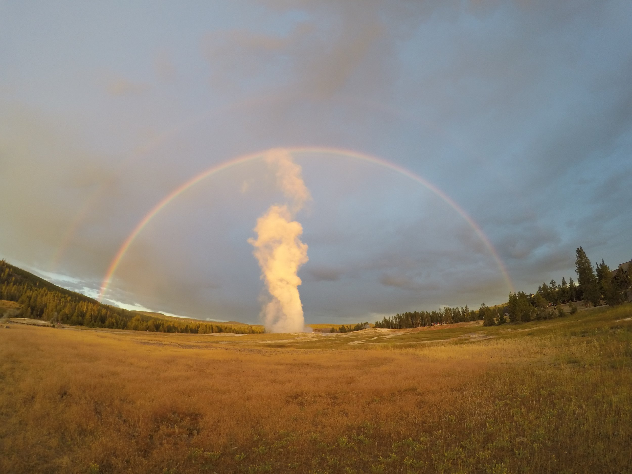 """Old Faithful going off under not one but TWO rainbows.  """"A double rainbow, but what does it mean""""??"""