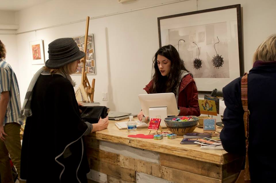 Campos, who now manages the YI shop, helps a customer at February's First Thursday Extravaganza.