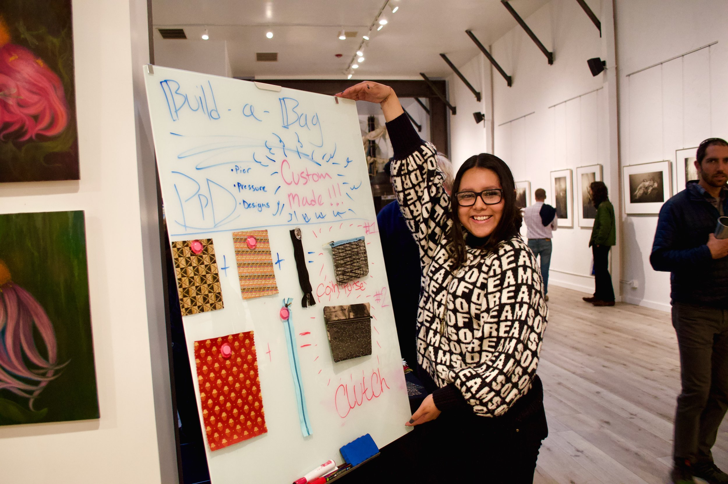 Mayte posing in front of a custom PPD bag sign at 1st Thursday