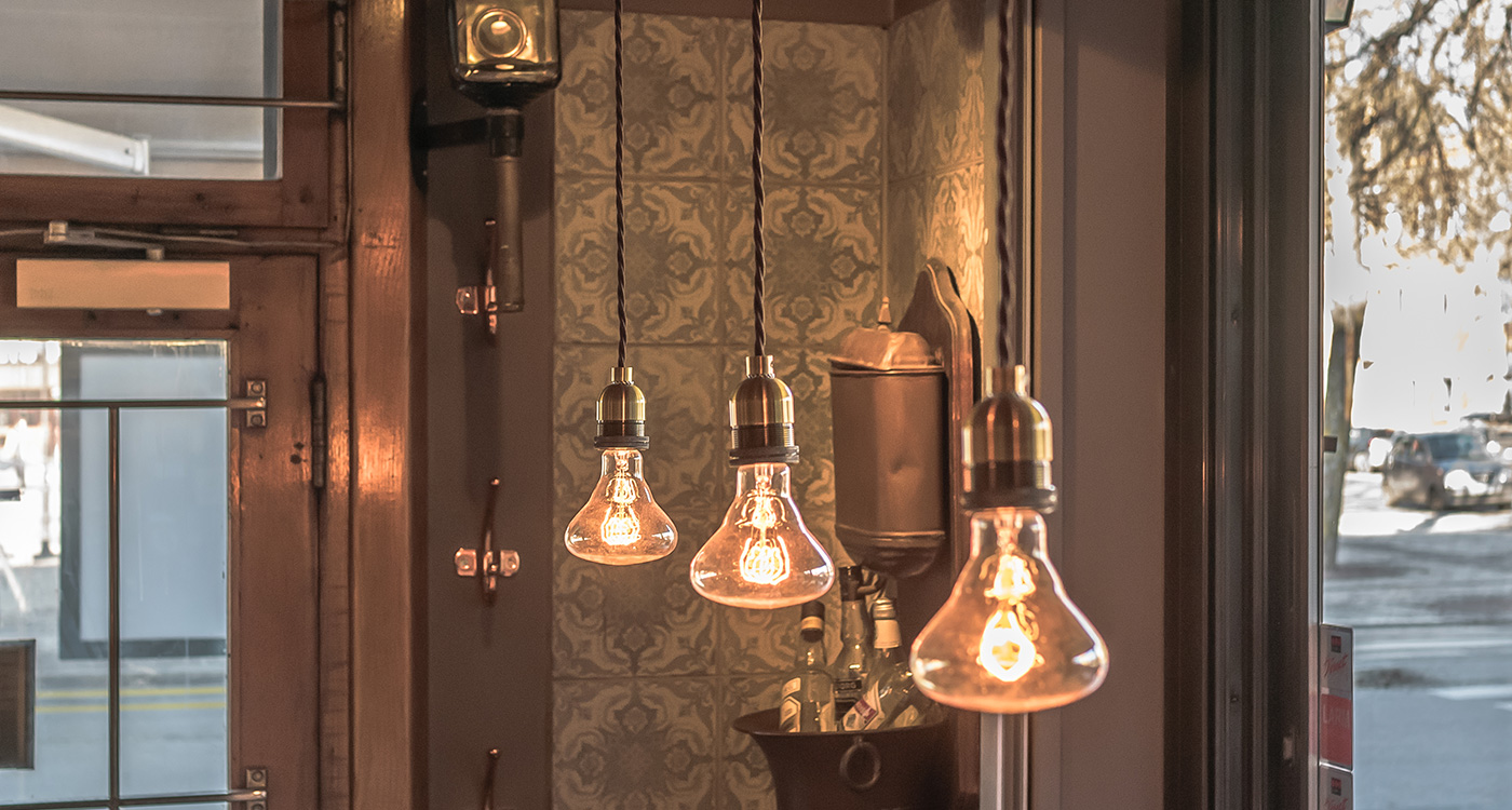 Rusty Remakes Authentic Brass Pendants with Authentic Carbon Filament Bulbs Joseph above all tables.