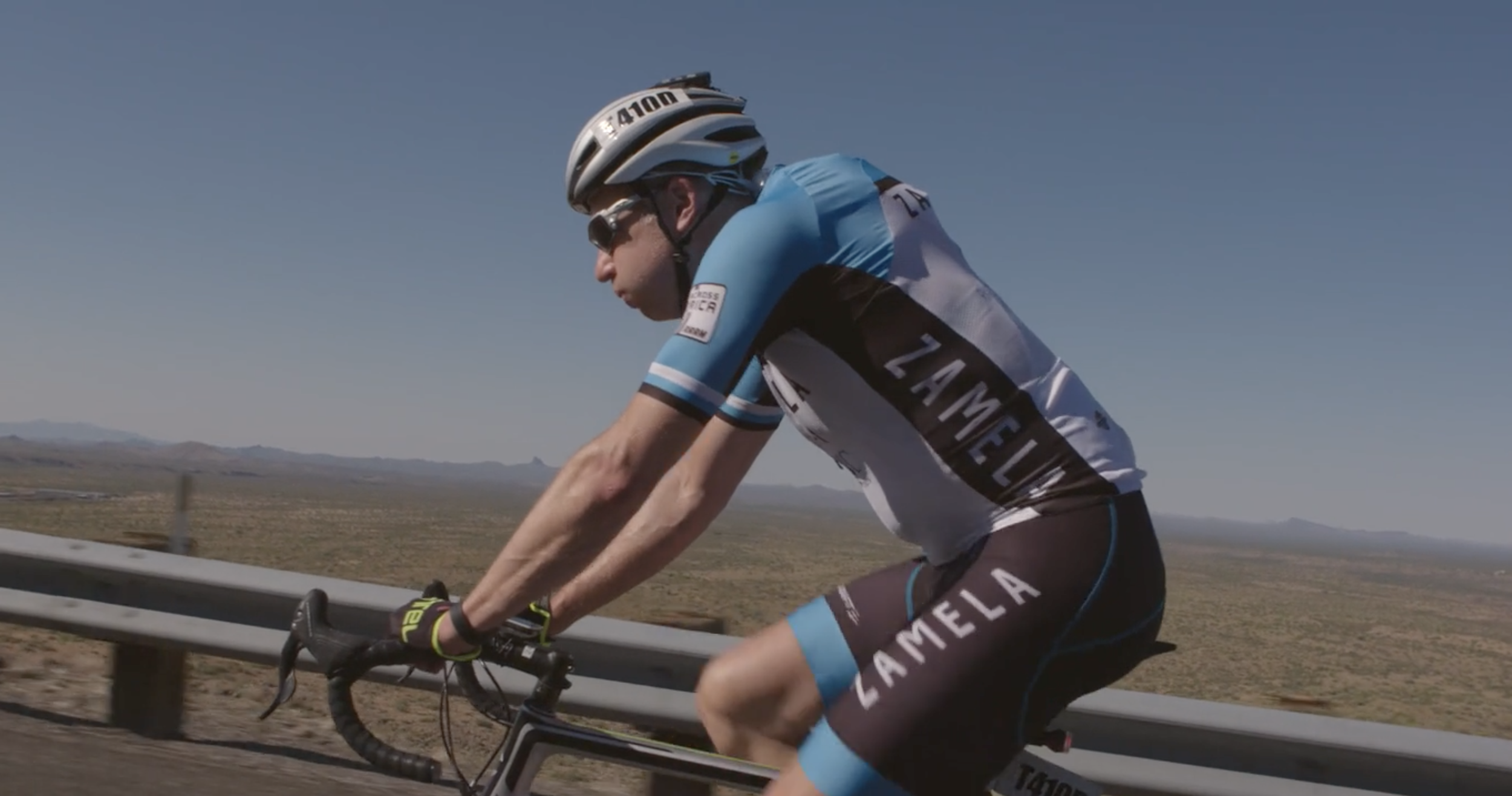 Matt Puomo riding uphill in the heat of the desert.