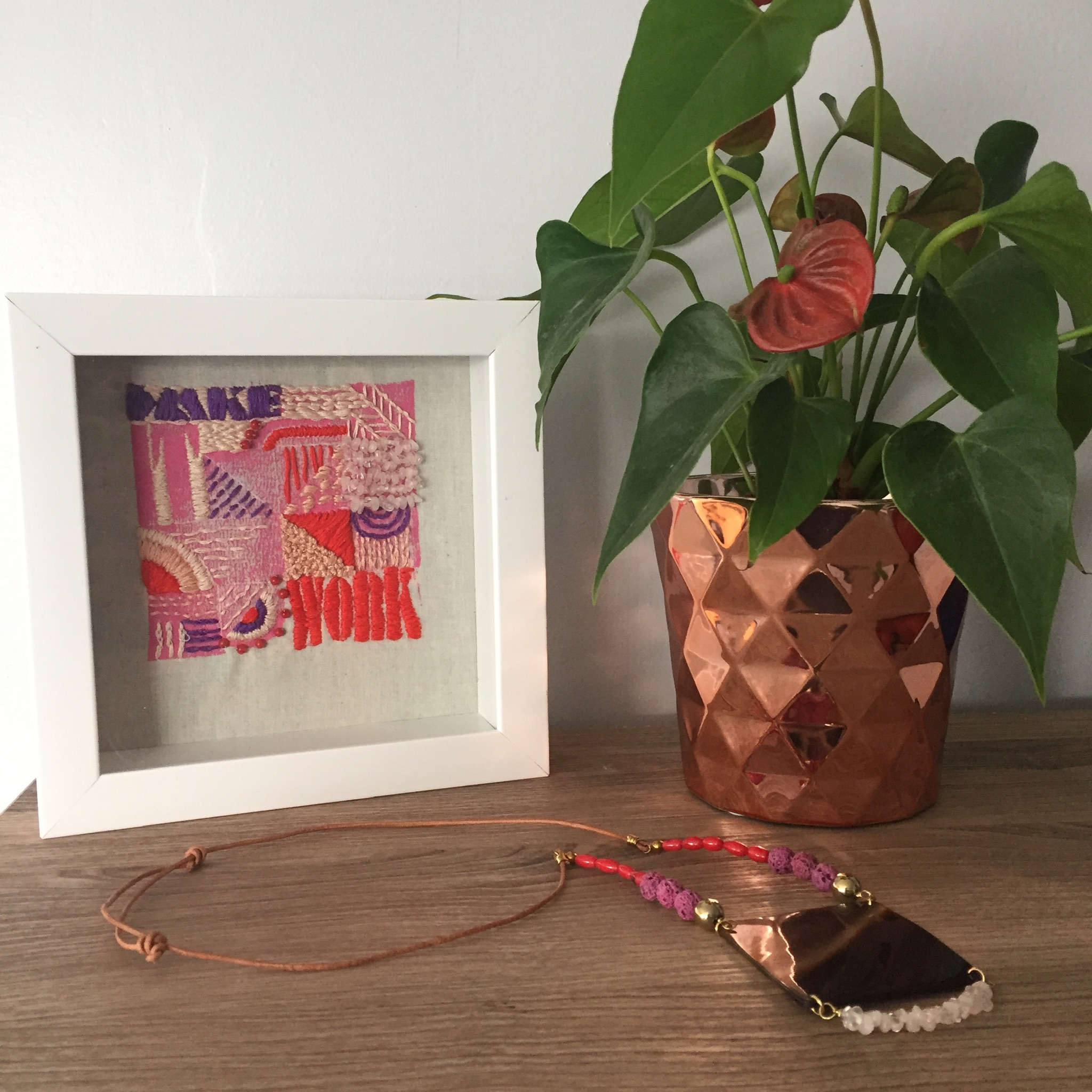 """Make It Work"" embroidered block print on cotton with rose quartz and red coral. Taken in my home next to my plant and one of my necklaces .JPG"