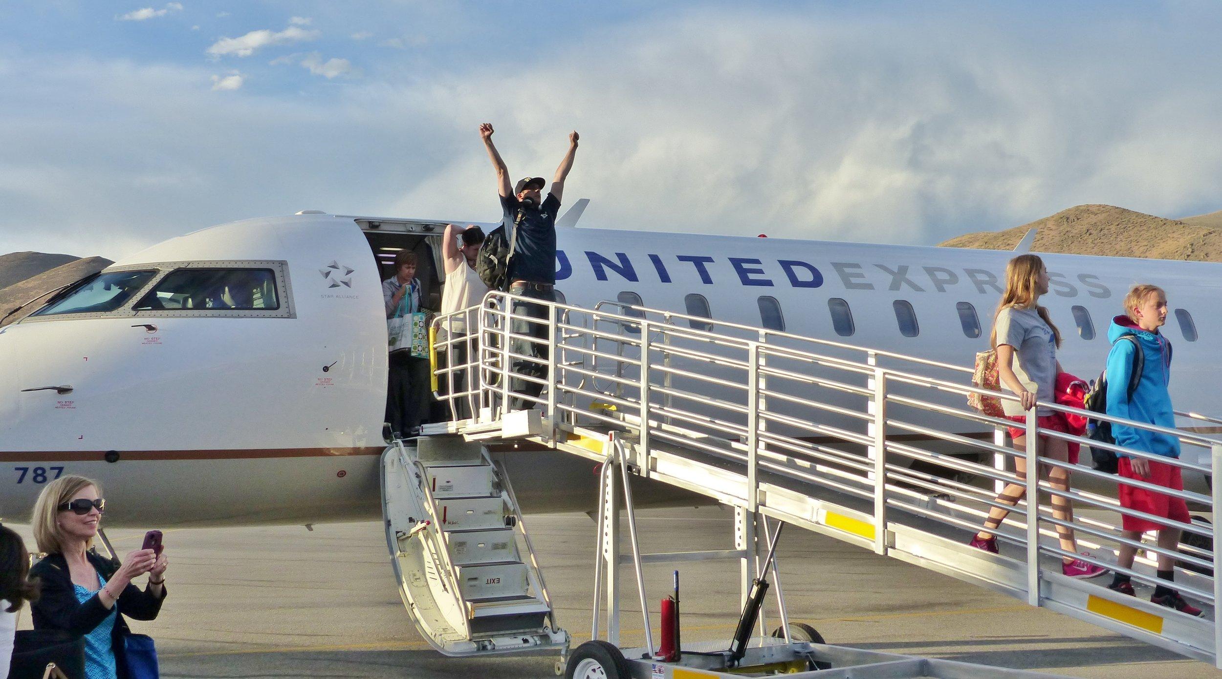 United DEN flight passenger celebrates. Credit Carol Waller 2014.JPG