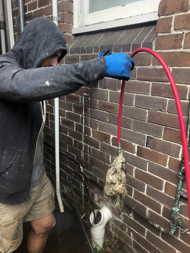 Our Sydney plumber pulling out a clump of wet-wipes from a blocked sewer drain in Sydney.