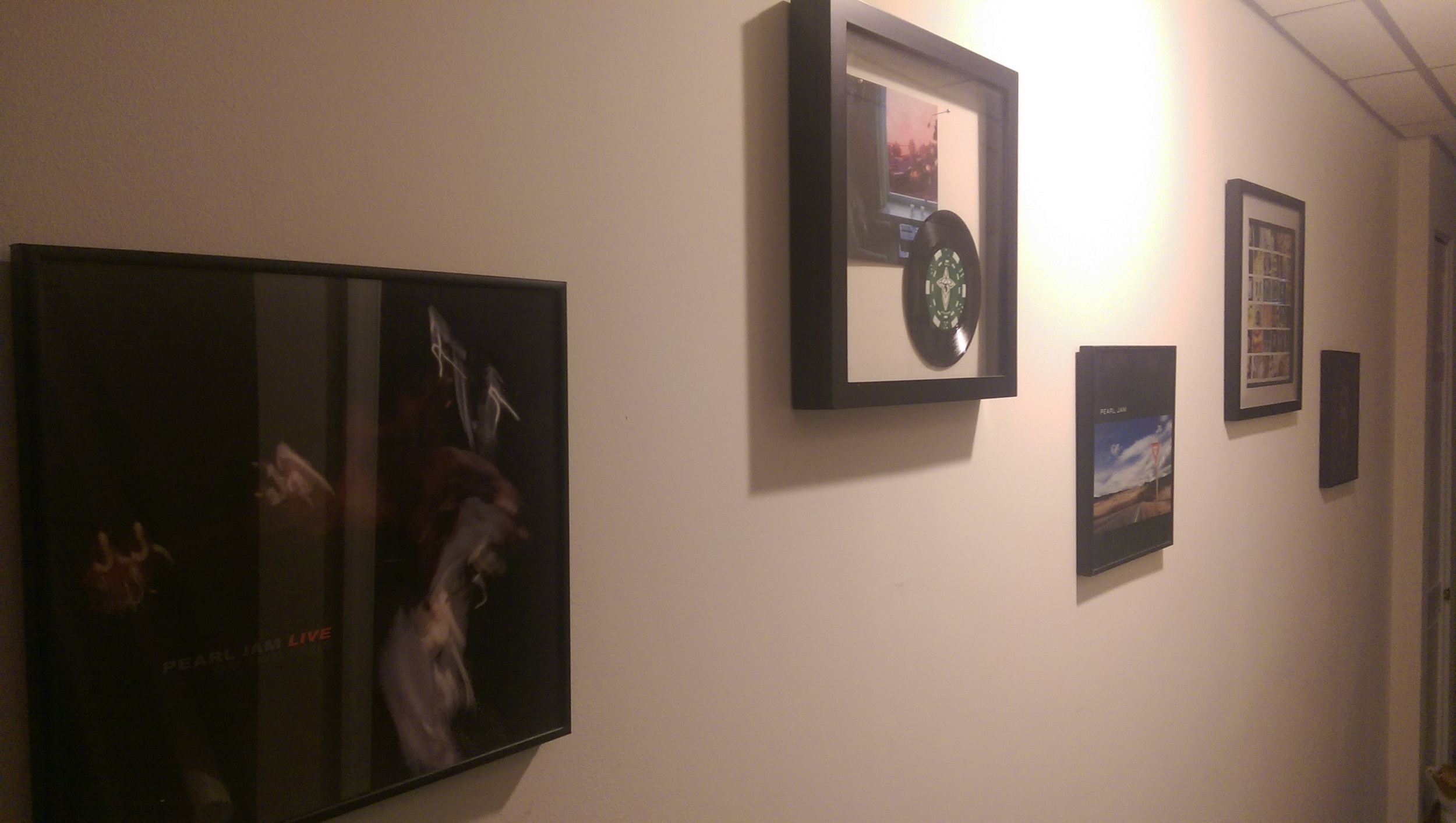 Framed Peal Jam vinyls covering the basement walls