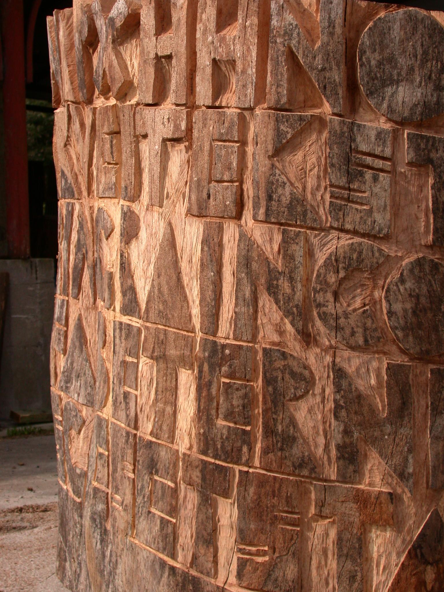 """Et nærbillede af skriften på skulpturen lige da den blev skabt. Bemærk at bogstavernes relief er dybest i toppen og bliver mindre nedover og nederst er kun træets egen """"skrift"""" tilbage."""