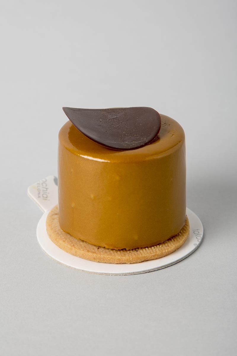 Galleta de limón,bizcocho, crema de limón, plátano caramelizado,mousse de chocolate con leche Jivara al 40%y baño de chocolate con leche.