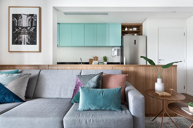A cozinha do apartamento ganhou toque de cor na marcenaria e a produção de almofadas nos mesmos tons fez o link com a sala de estar.  Foto @triadphoto  #sala #cozinha #living #kitchen #cozinhagourmet