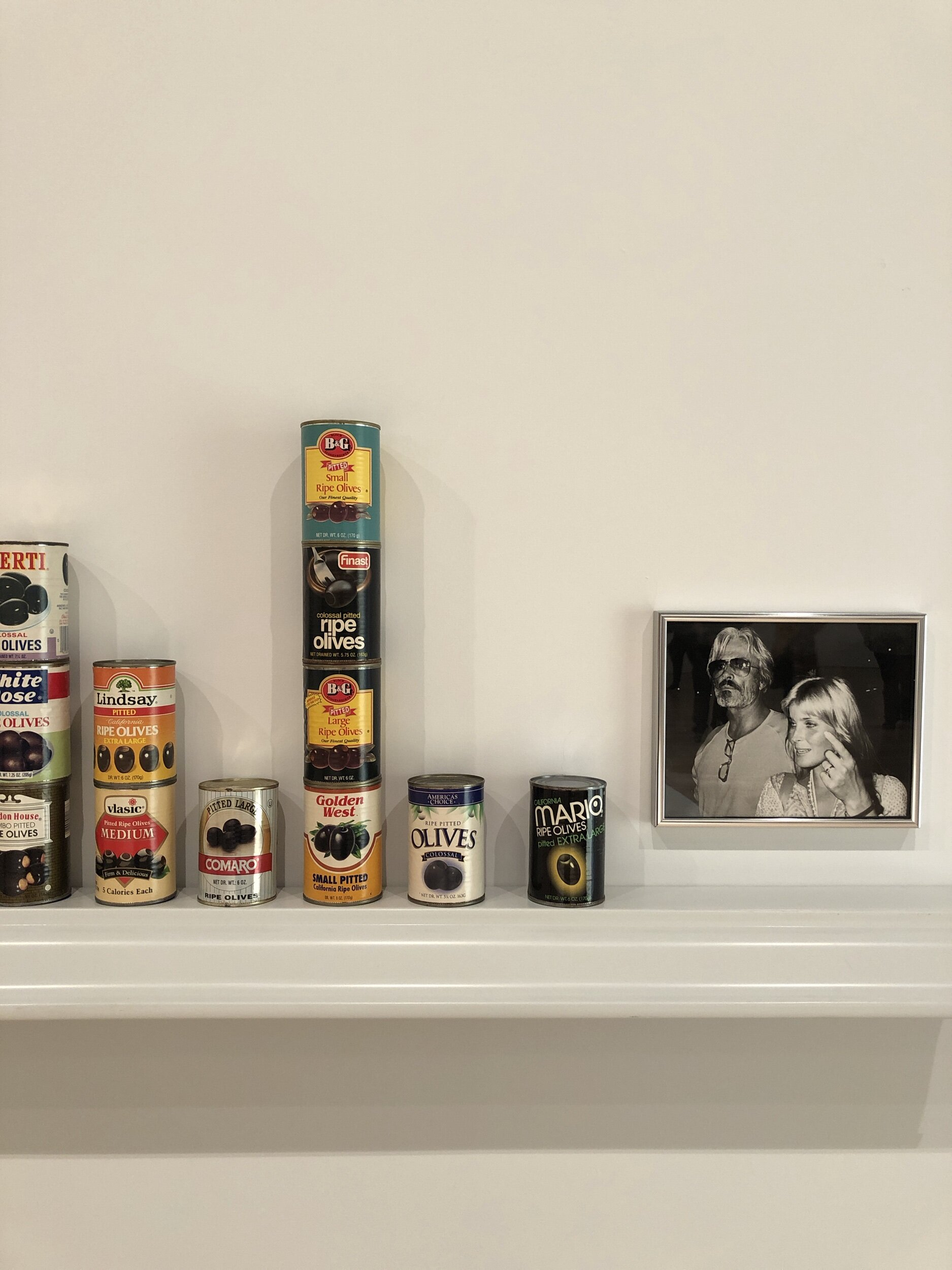 Teaching Bo to Count Backwards, 1996-97   This gallery contains Harrison's work from the nineties when she was starting her career. In the Bo Derek piece there are cans of olives stacked on an inverted gutter with photographs of Bo Derek and her husband John. As you look at the cans from left to right you will notice that the number of olives depicted on the labels gradually decreases while the Bo's expression transforms at the same time. Her husband John's expression seems aloof while Bo becomes increasingly assertive. Bo Derek is probably most associated with the movie  10  which was her rating as a beauty and also references the manner of counting via the canned olives in an absurd way. Harrison is usually referencing art history in some way, and in this case we can see a relationship to Warhol's soup cans as well as the Minimalist focus on systems, especially systems of counting or recording and seriality in repetition.