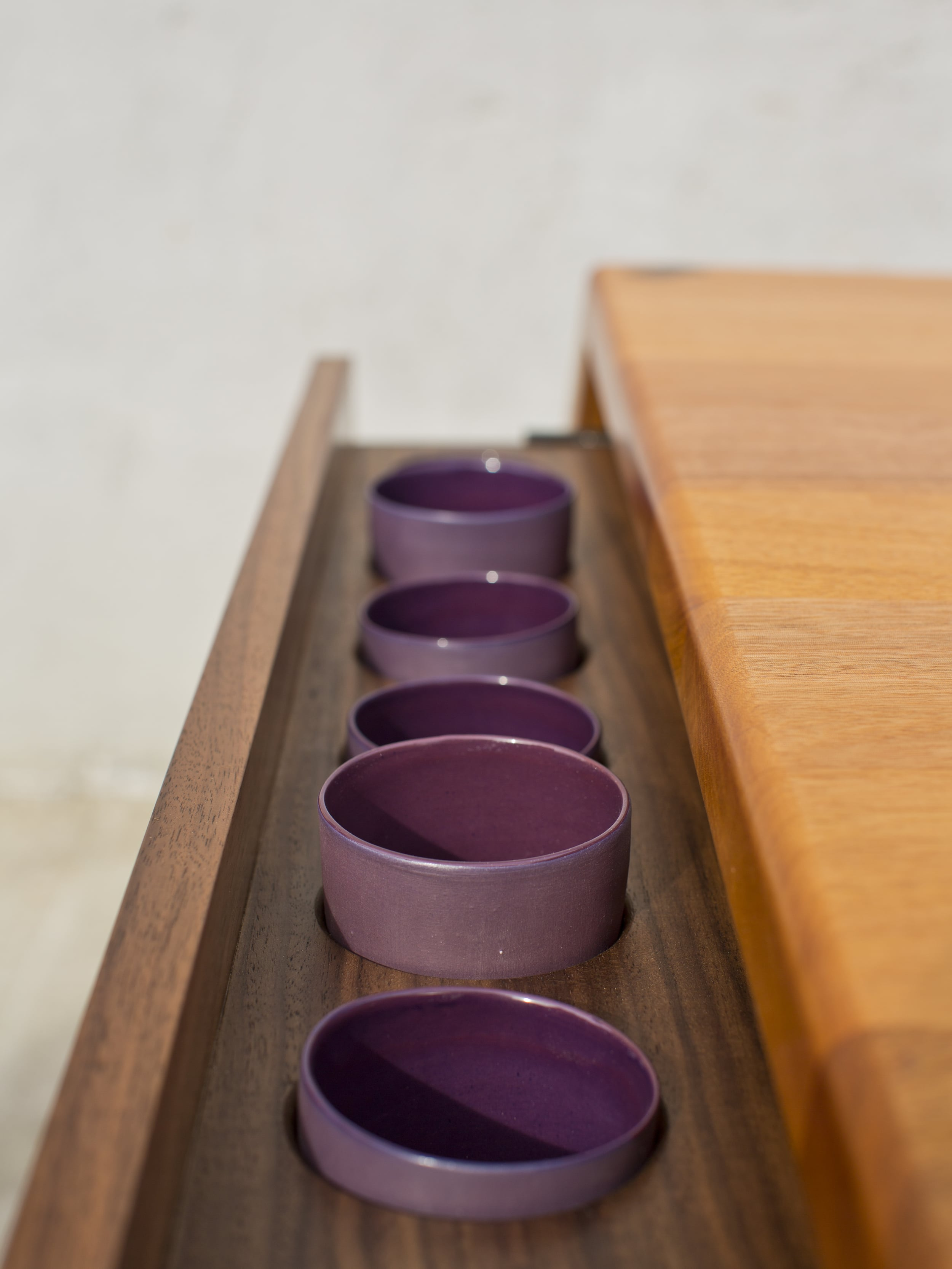 Handmade porcelain cups nest into a side drawer.