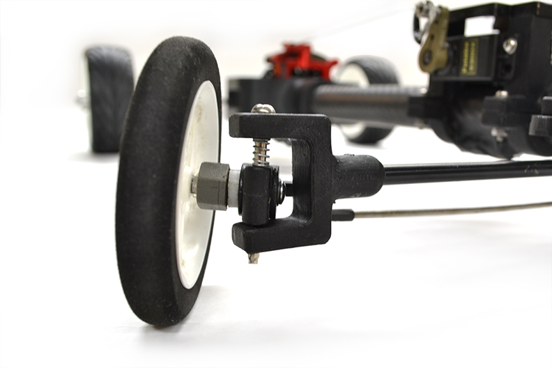 Independent suspension was designed not just for bumps but primarily to compensate for the force of a fully wound rubber band bearing down on one side. With added suspension, the car could hold more force and keep all four wheels on the ground.