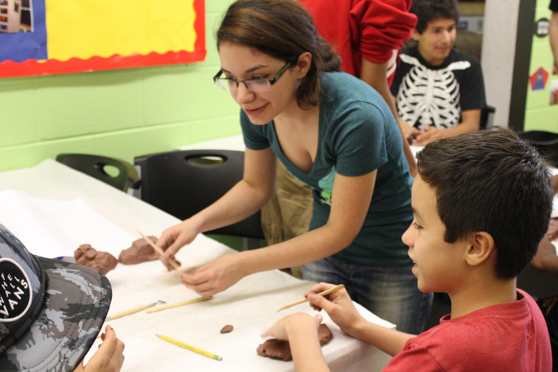 Team member, Atria Azarmi demonstrates clay carving tecniques.