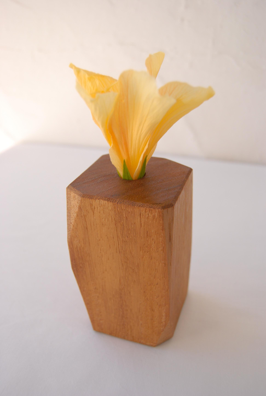 Iroko carved vase with yellow Hibiscus. /  Florero tallado a mano de madera de iroko con flor de hibiscus amarillo.