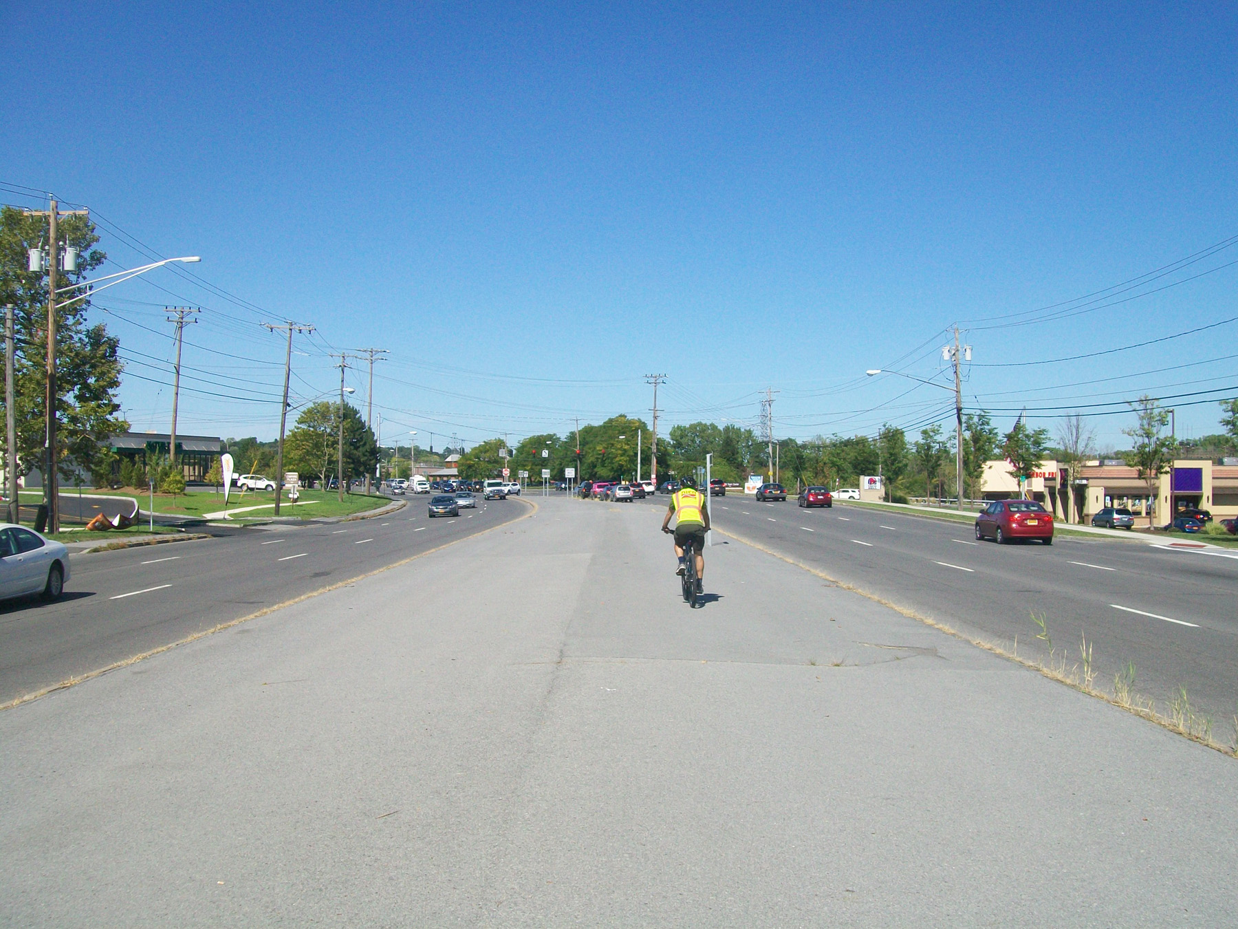 A cyclist rides down the middle of the asphalt median on Erie Boulevard East in DeWitt