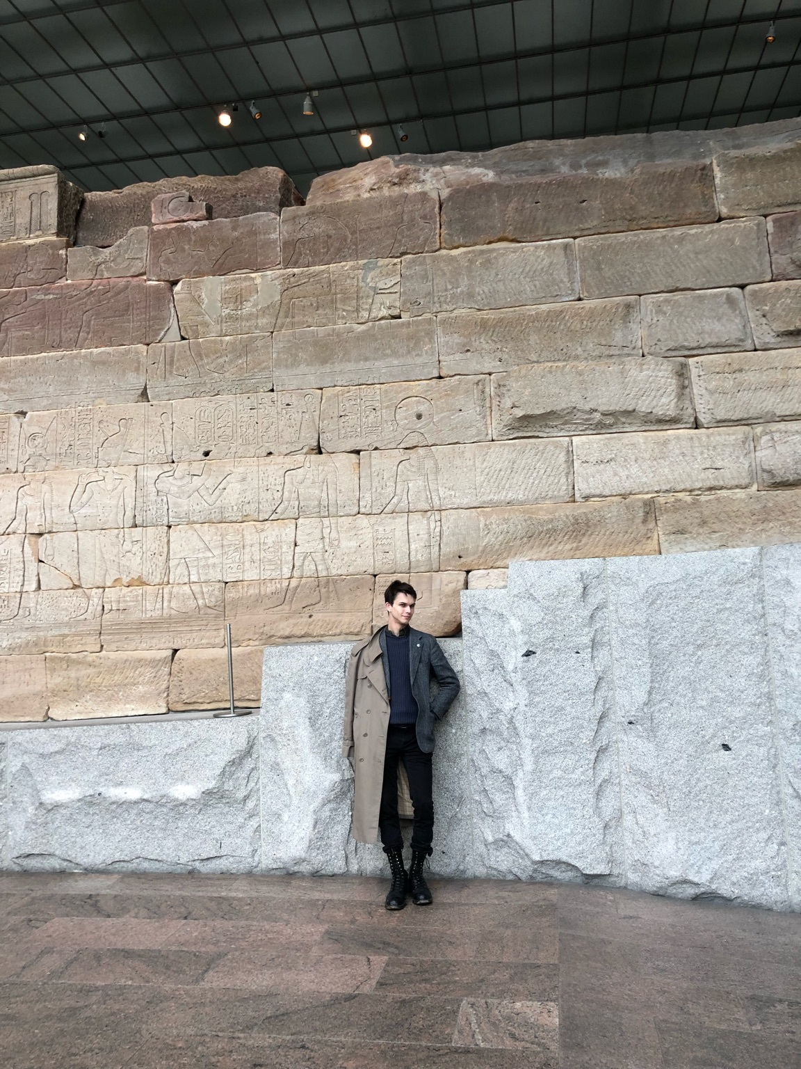 Myself, outside the Temple of Dendur, Metropolitan Museum of Art, Manhattan, February 2019. The carvings behind me show the Imperator Augustus making offerings to various deities of the Egyptian pantheon.