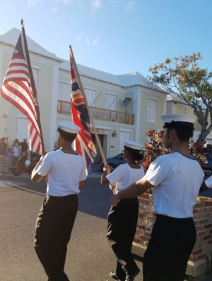 The T.S. Admiral Somers Sea Cadets of Bermuda lead the procession from the town square to St. Peter's Church in St. George's Parish, Bermuda, where the wreath-laying ceremony takes place. They carry the flag of Bermuda and the flag of the U.S. with 13 stars.