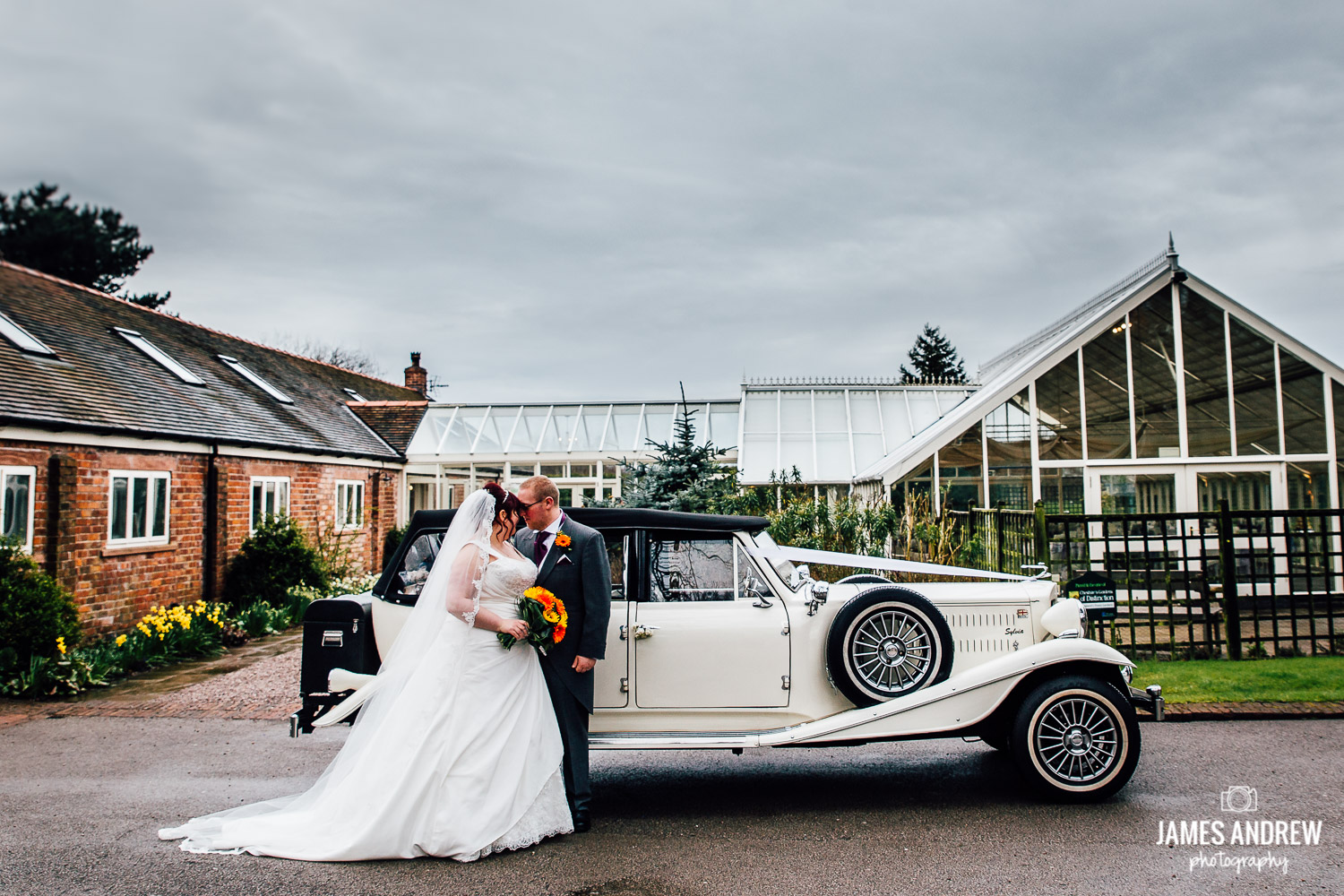 bride and groom with vintage wedding car at abbeywood estate cheshire