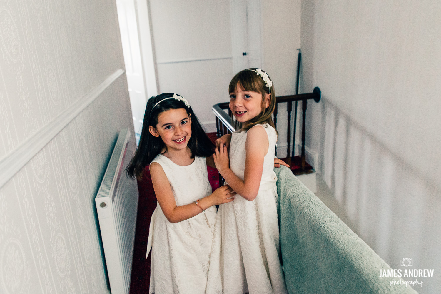 bridesmaid and flower girl playing on stairs