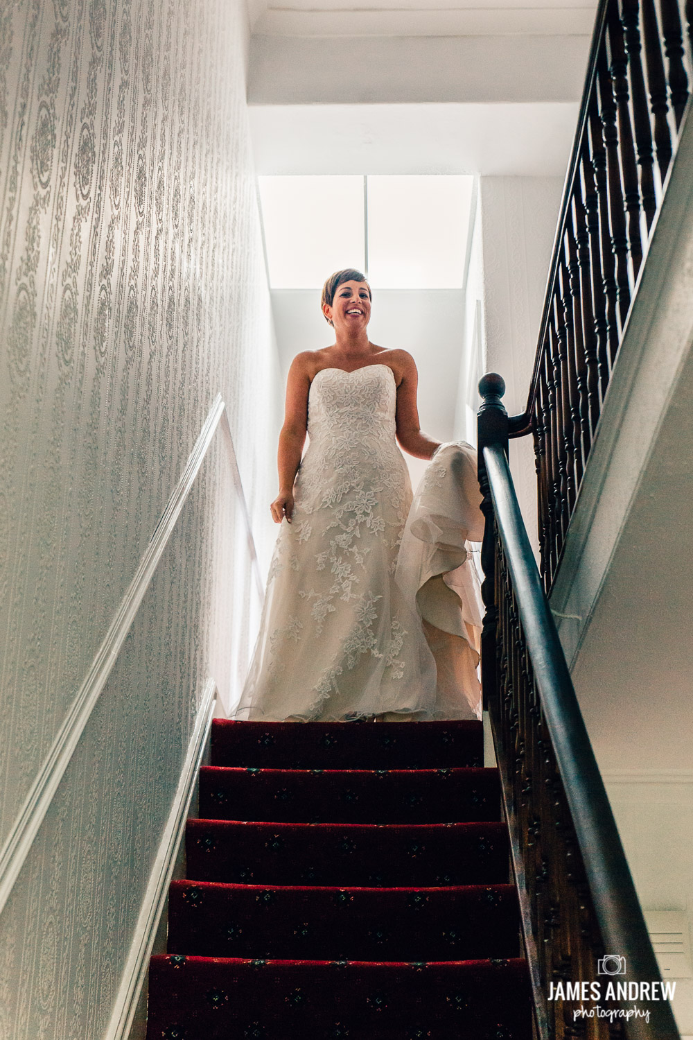 bride in wedding dress at the top of staircase bright light