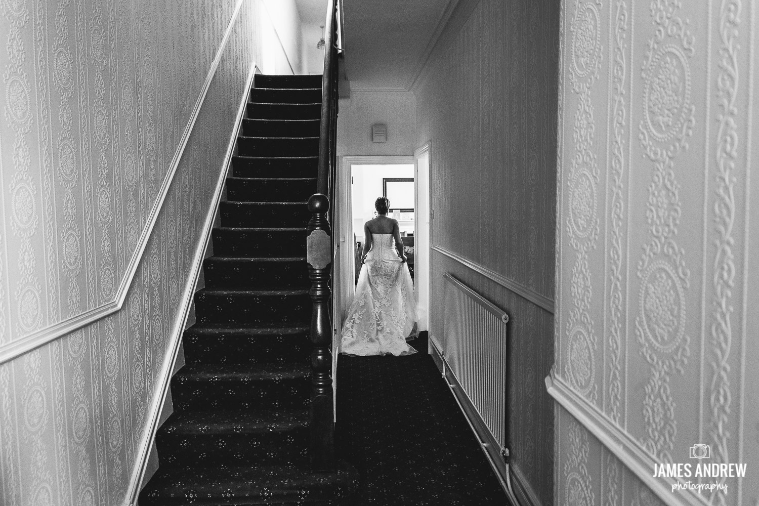 bride walking down hallway in black and white