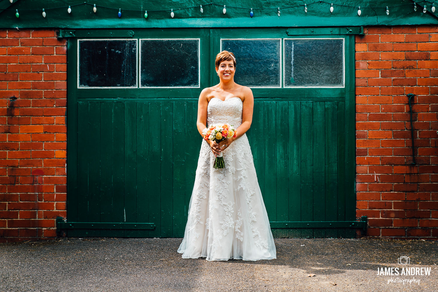 vintage bride stood in front of green door  with flowers